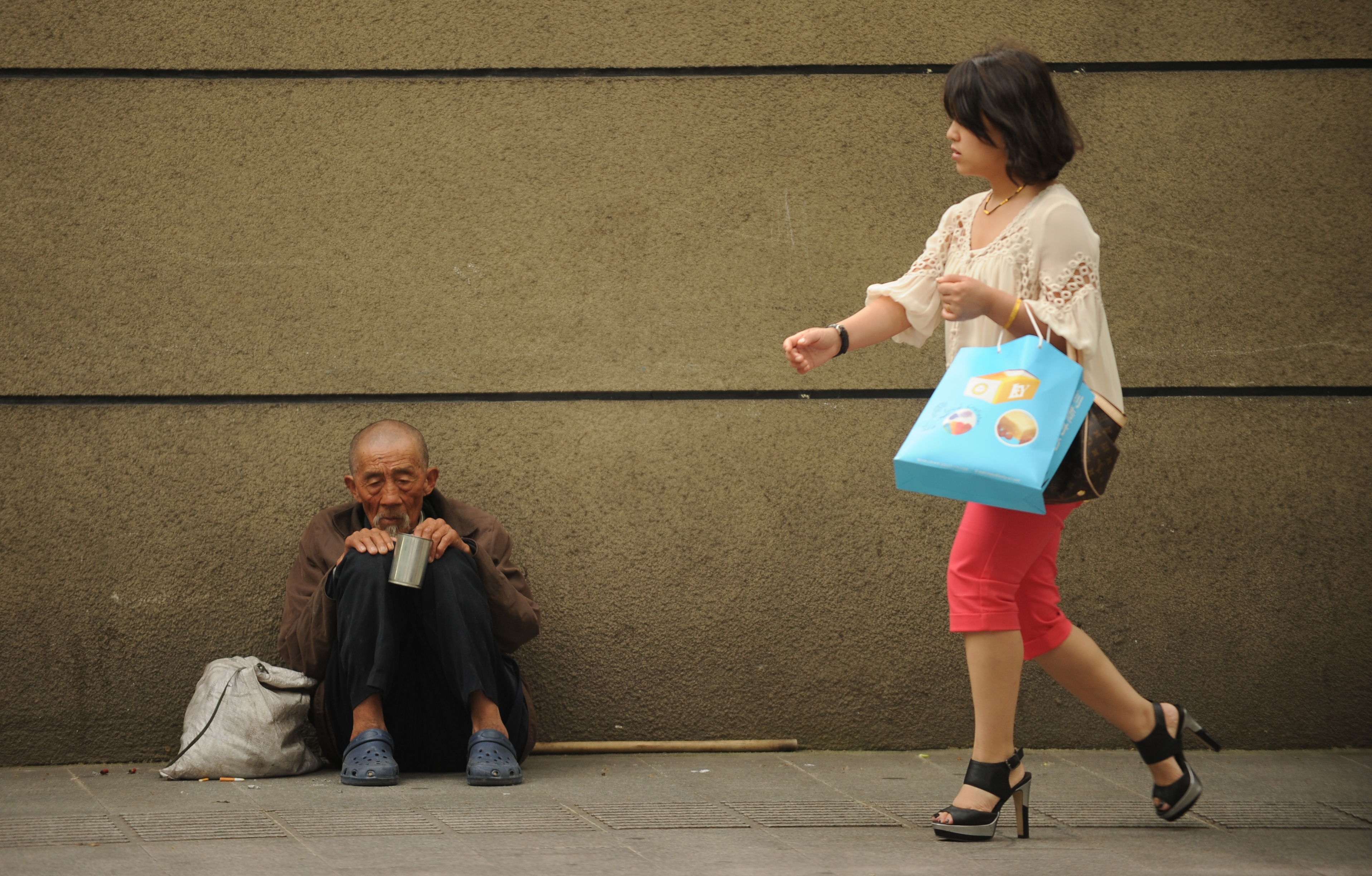 A man begs on a street as a woman passes