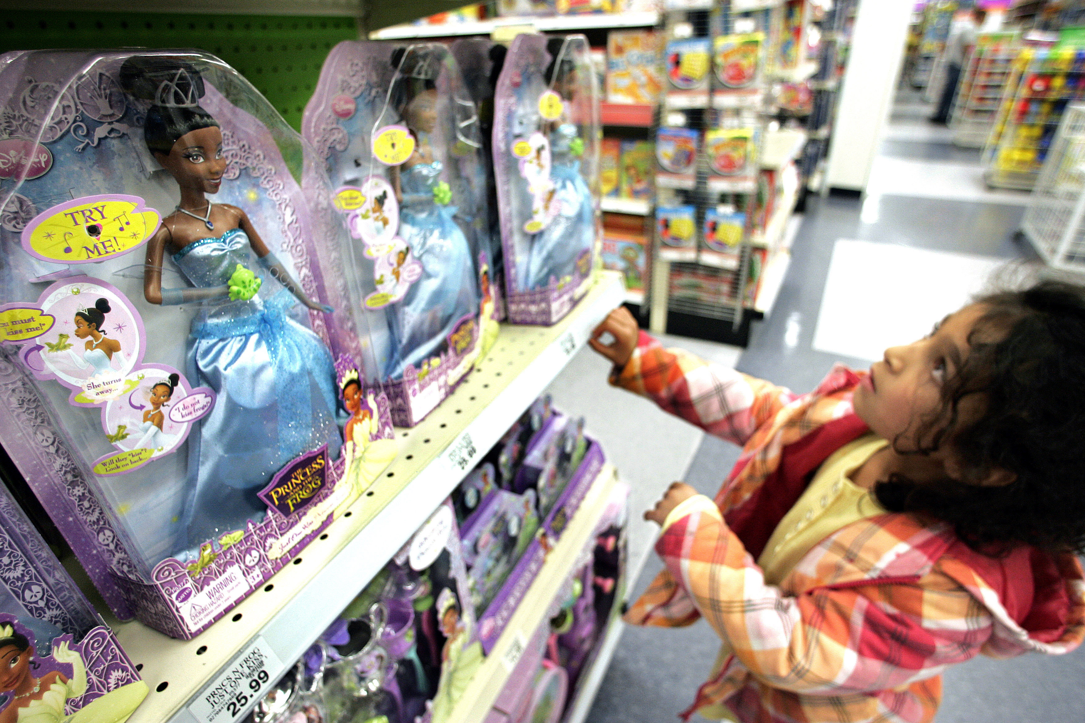 A young girl looks at a doll based on the Disney animated film, The Princess and the Frog.