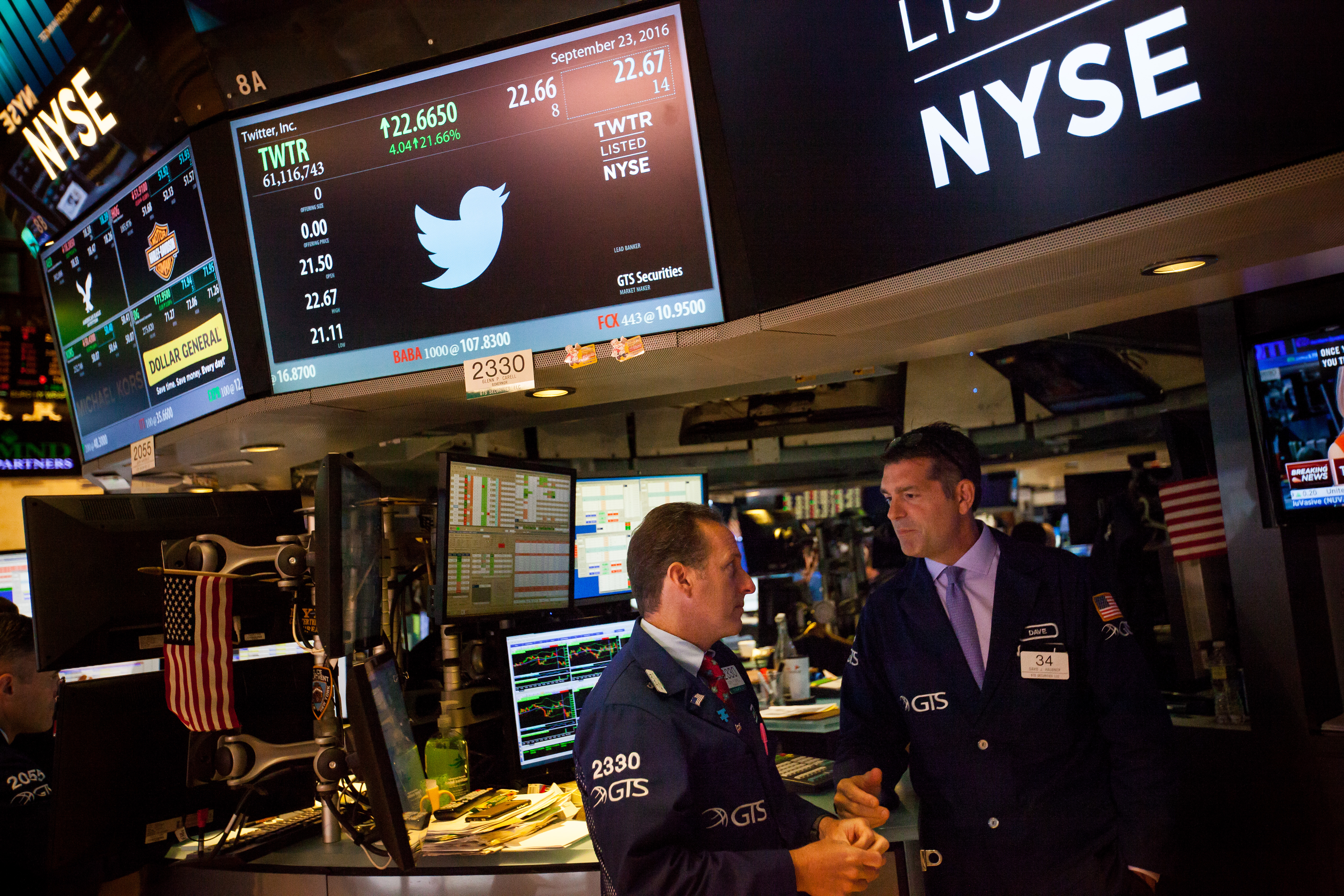 Stock traders work beneath a monitor displaying Twitter Inc. signage on the floor of the New York Stock Exchange (NYSE) in New York, U.S.