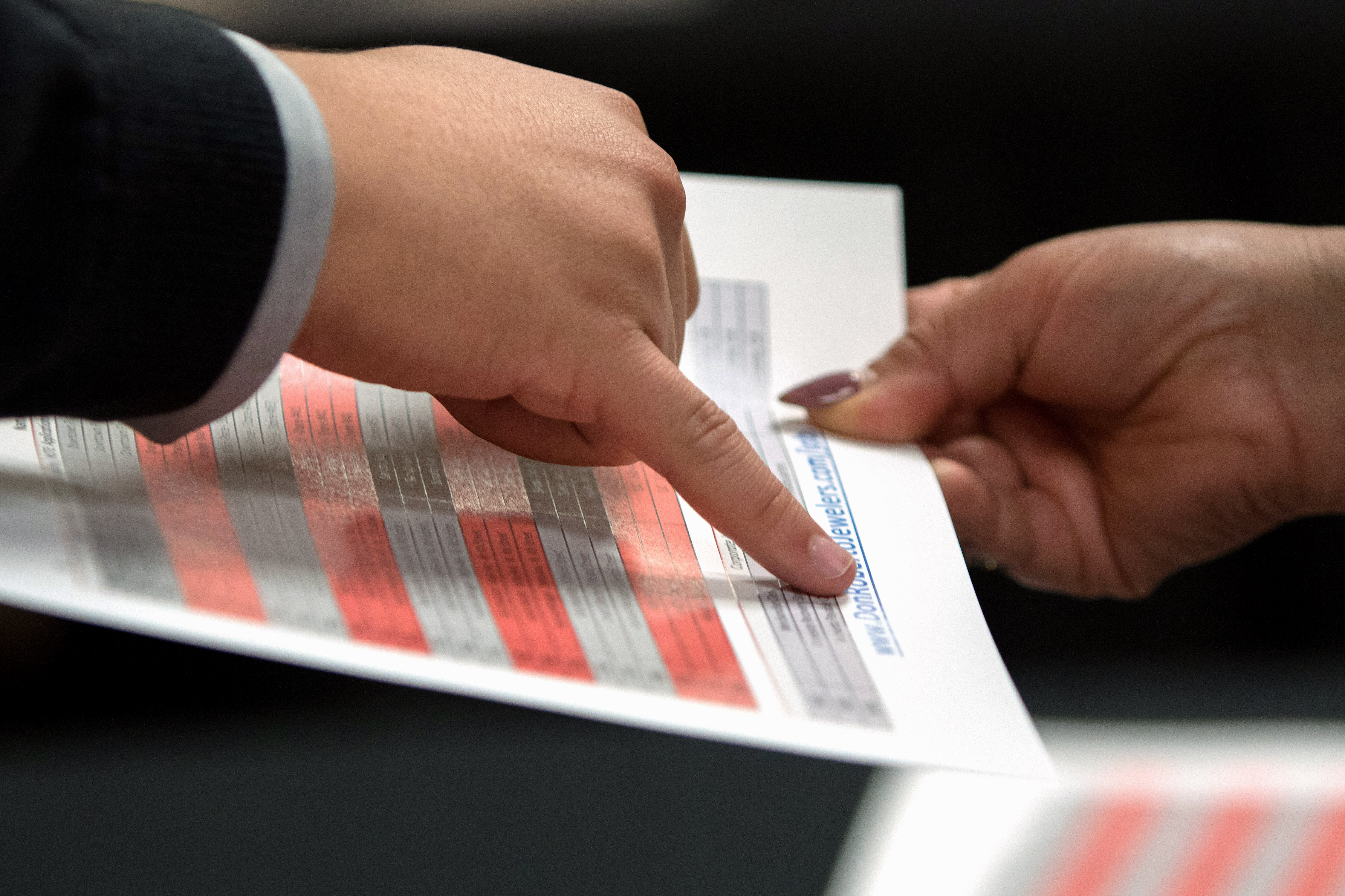 A representative goes over a pamphlet with a job seeker during an Orange County Choice Career Fair in Santa Ana, California, U.S., on Thursday, Oct. 6, 2016.