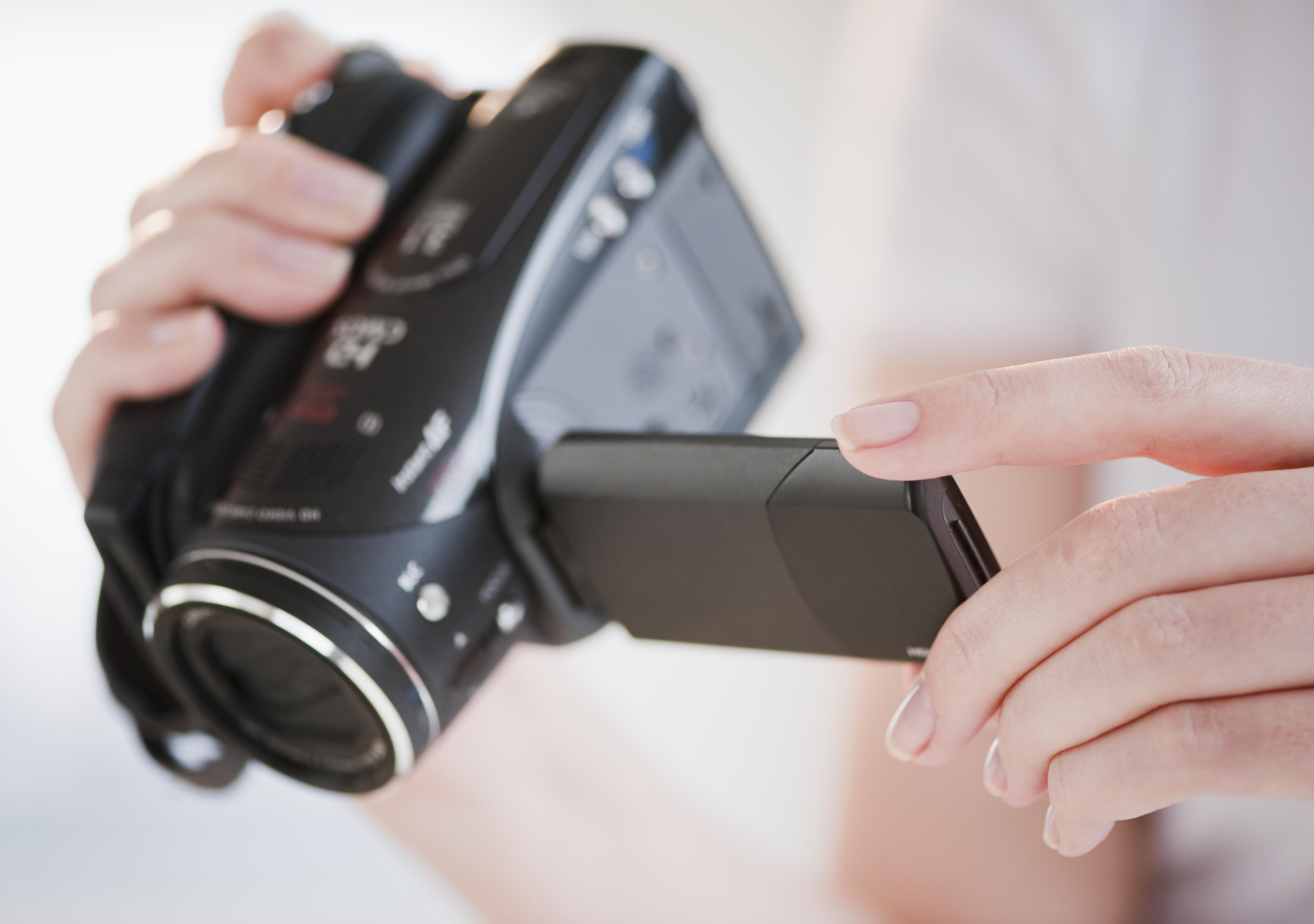 Woman using digital camcorder, close-up