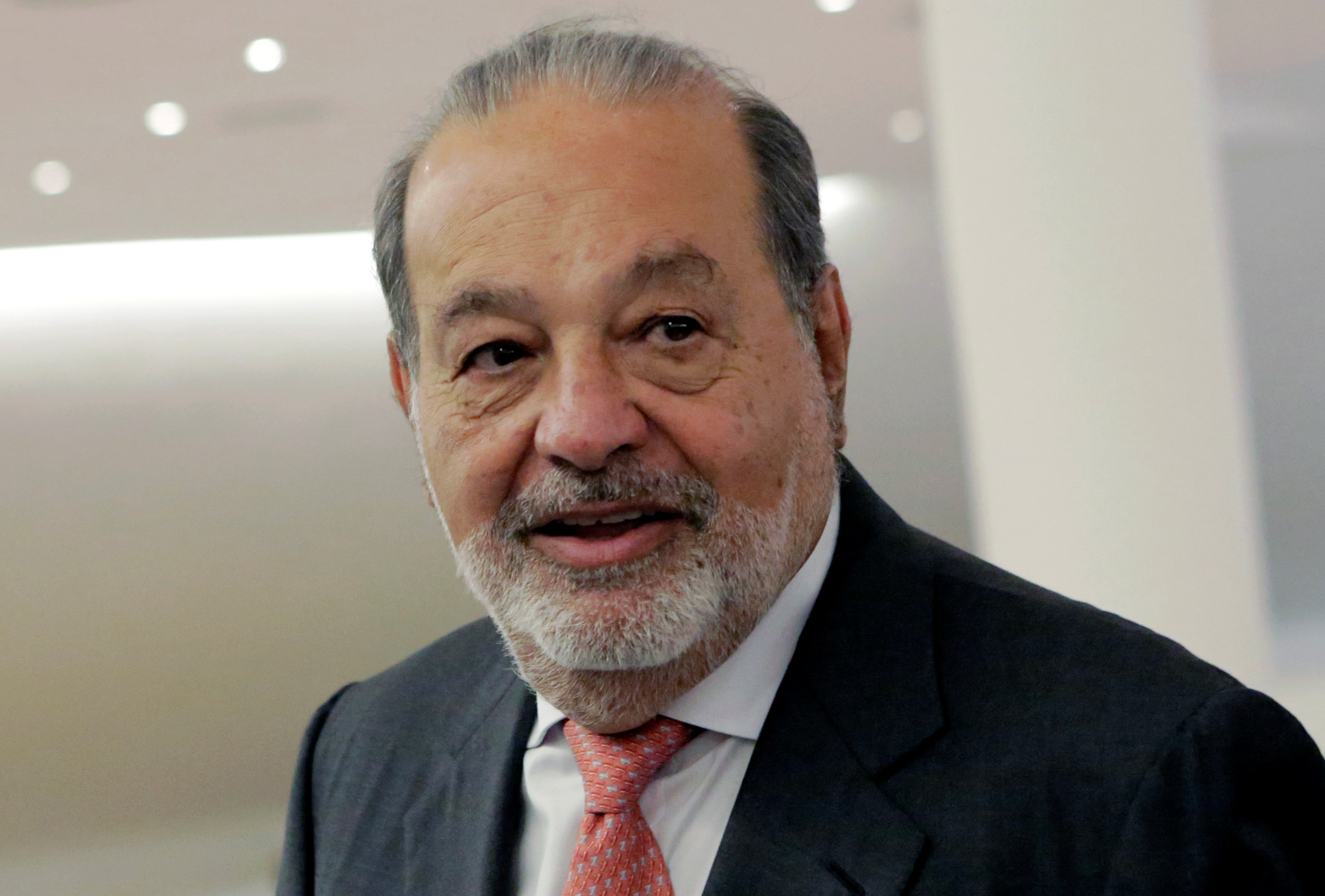 Mexican tycoon Carlos Slim walks after he launched a free online platform for education with free access to mobile WiFi connections to the Internet on his Infinitum service during a news conference at Soumaya museum in Mexico City