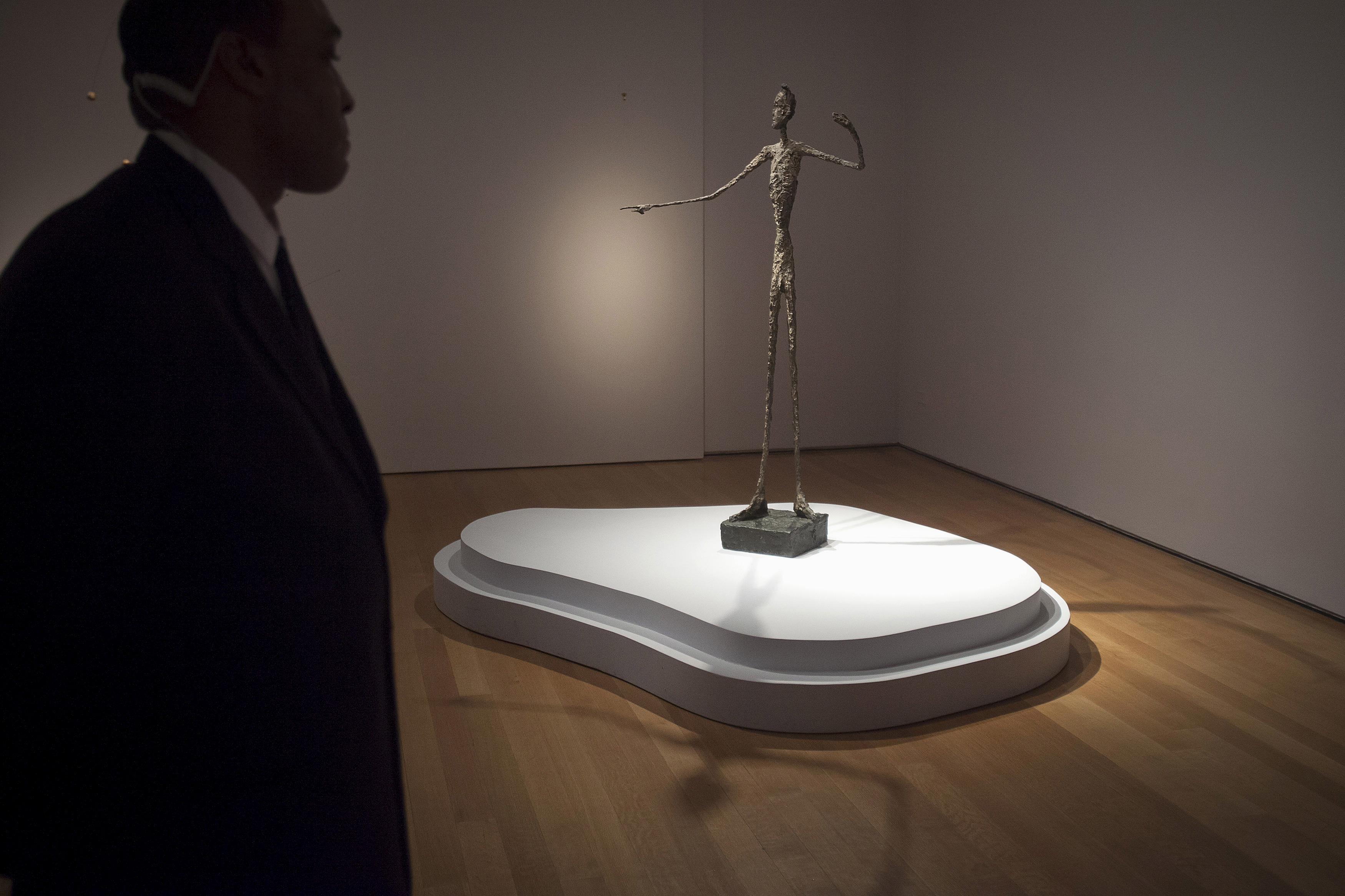 "A guard stands watch over Alberto Giacometti's ""L'homme Au Doigt"" (Pointing man) sculpture at Christie's Auction House in the Manhattan borough of New York"