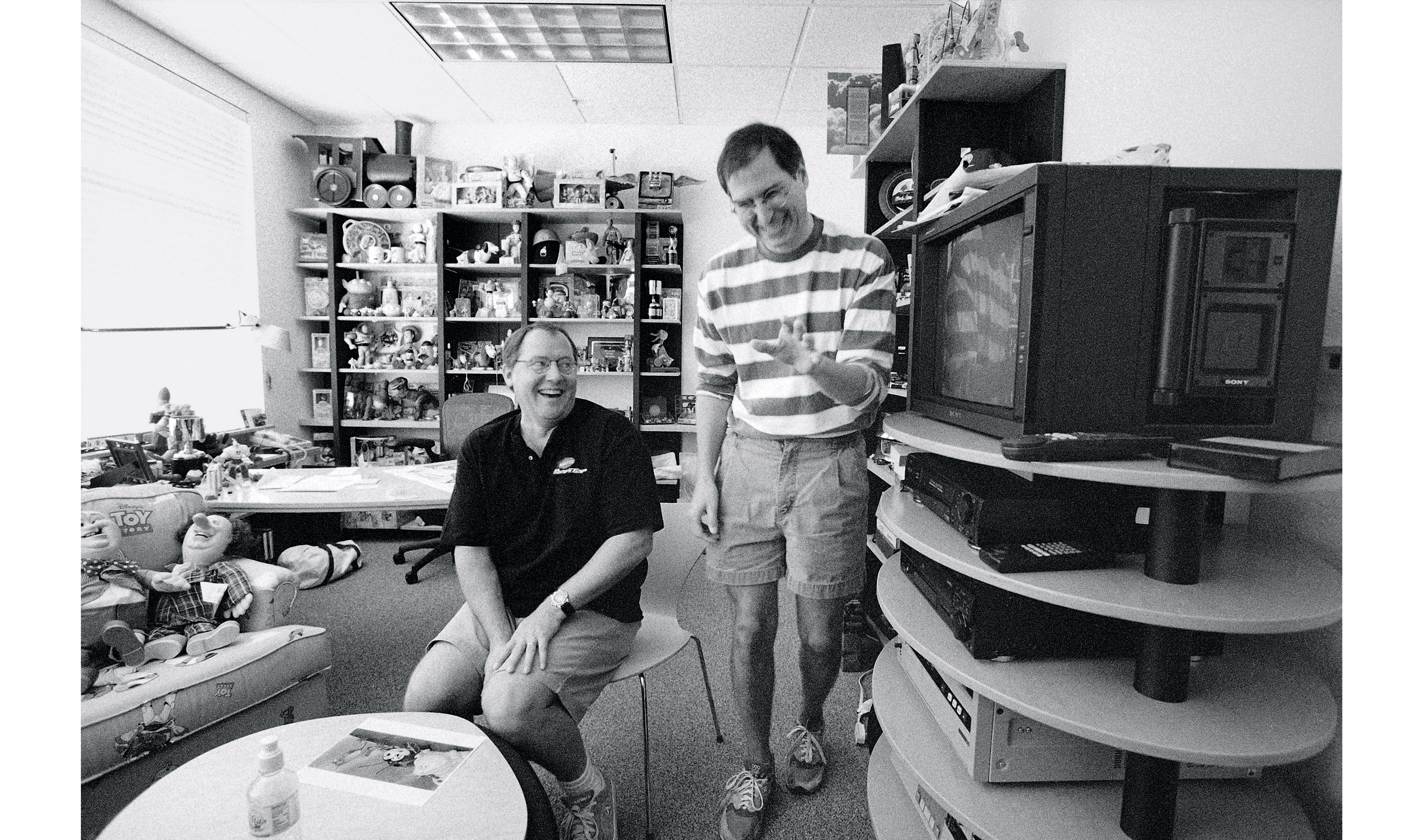 Jobs laughs with Chief Creative Officer John Lasseter in the latter's office at Pixar in August 1997.