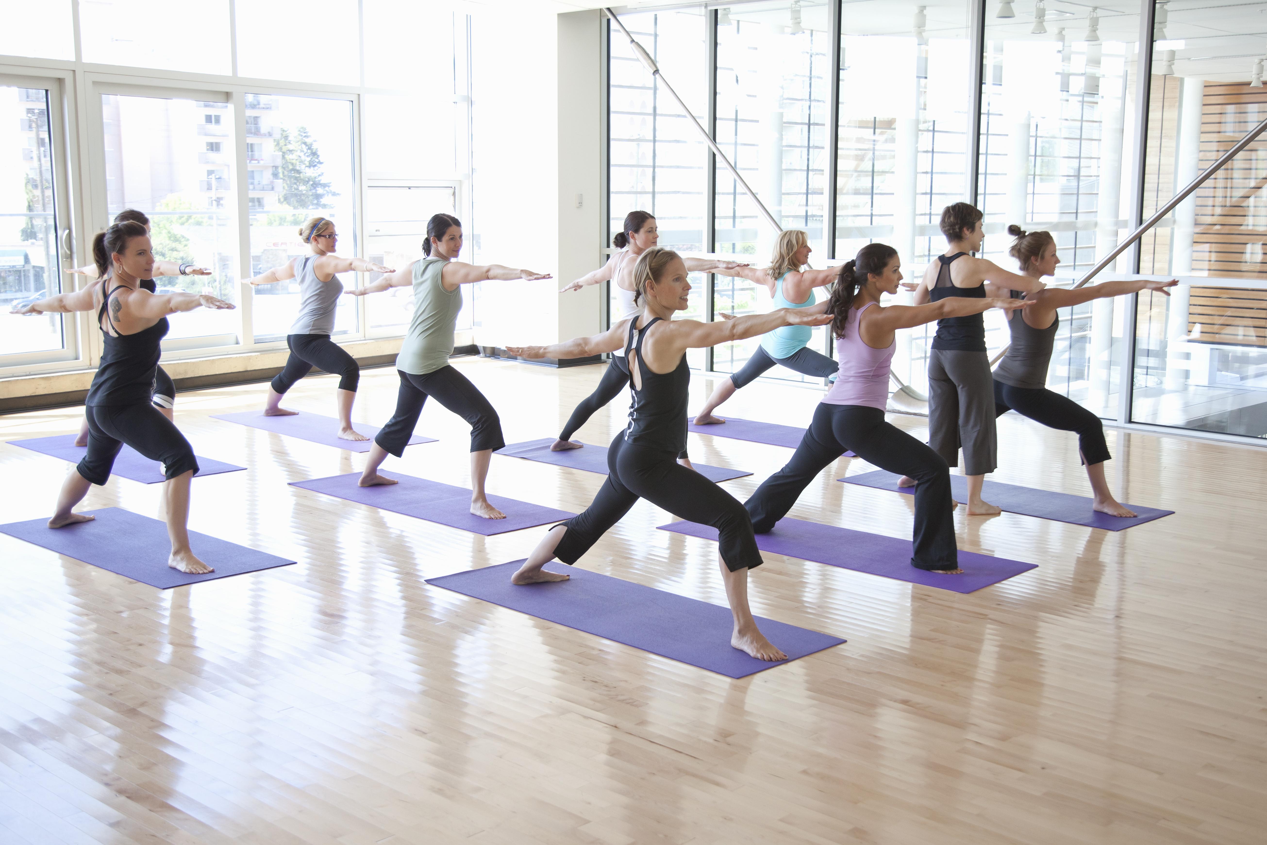 Yoga instructor guiding class through poses