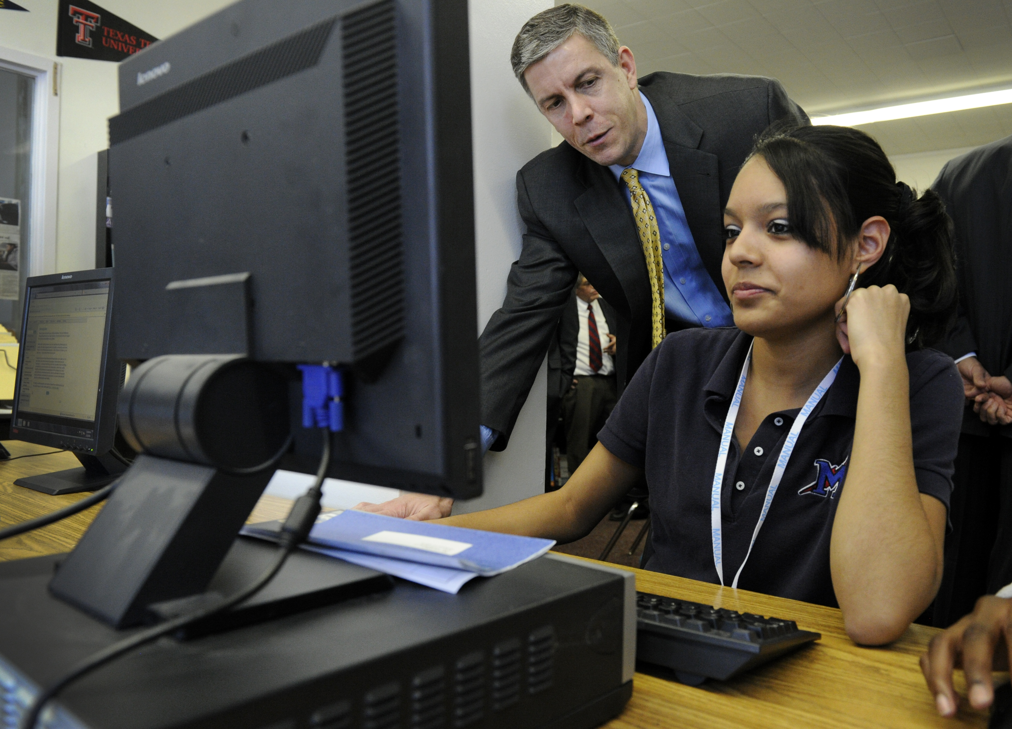 DENVER, CO--U.S. Secretary of Education, Arne Duncan, left, talks with Manual High School student, Karen Santoyo, 18-years-old, as she works on the computer at the Futures Center looking at colleges and financial aid Tuesday morning. Duncan held a communi