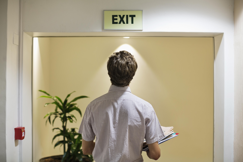 Businessman examining ëexití sign in office