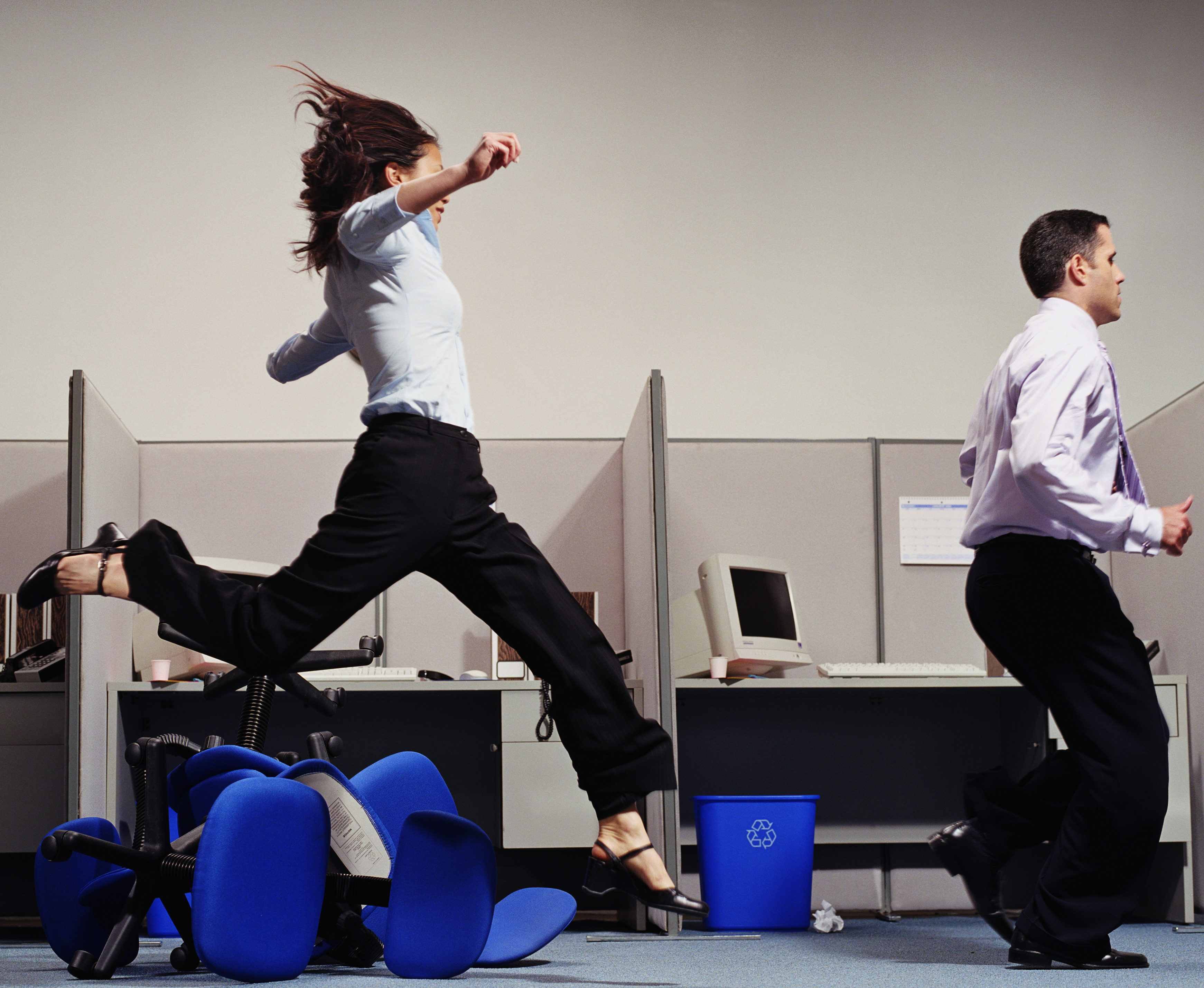 Man and woman running through office, hurdling chairs