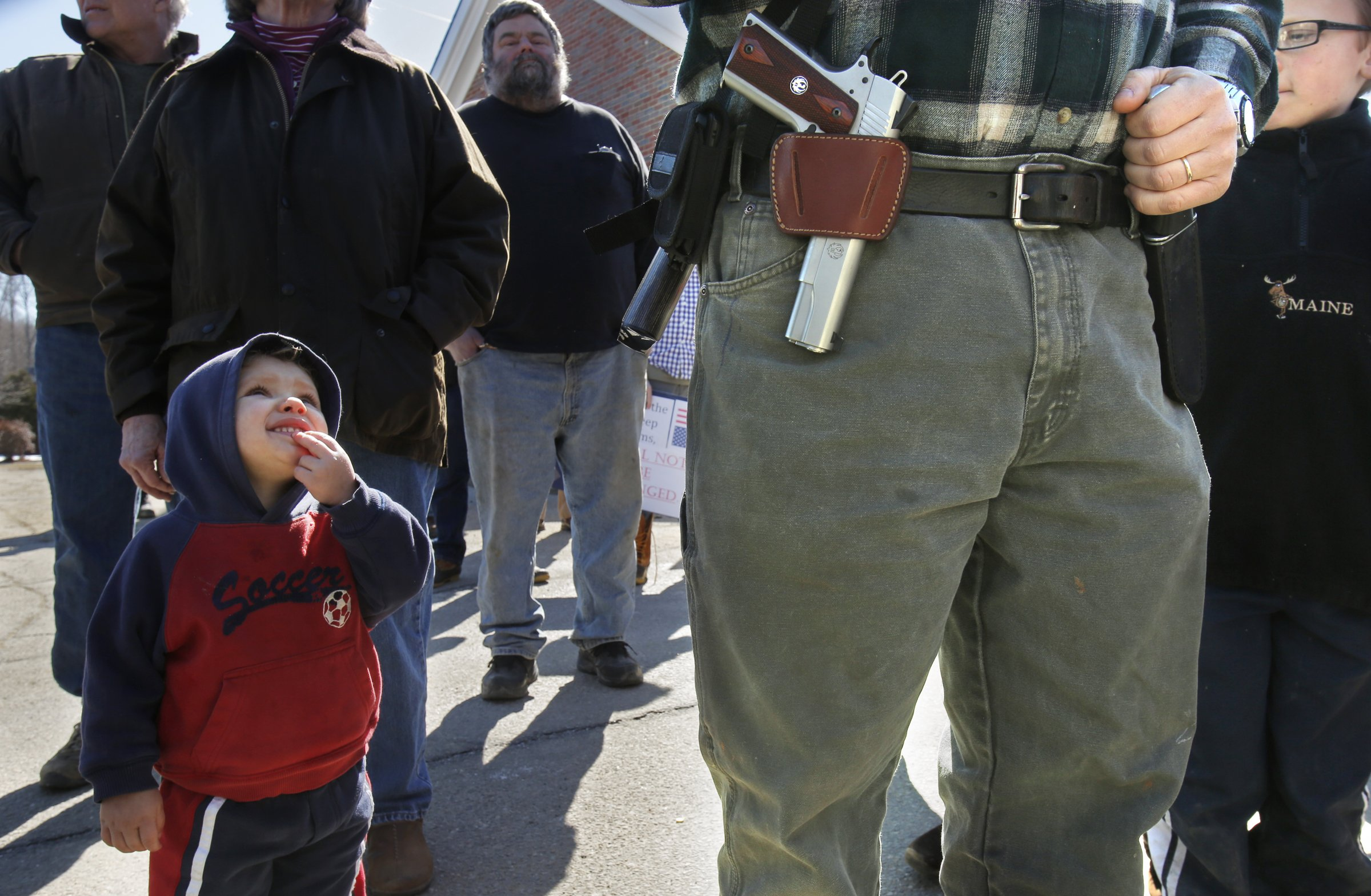Samson Hiltz, 2, looks up to his father Jeremy Hiltz of Chelsea while the two attend a rally protest