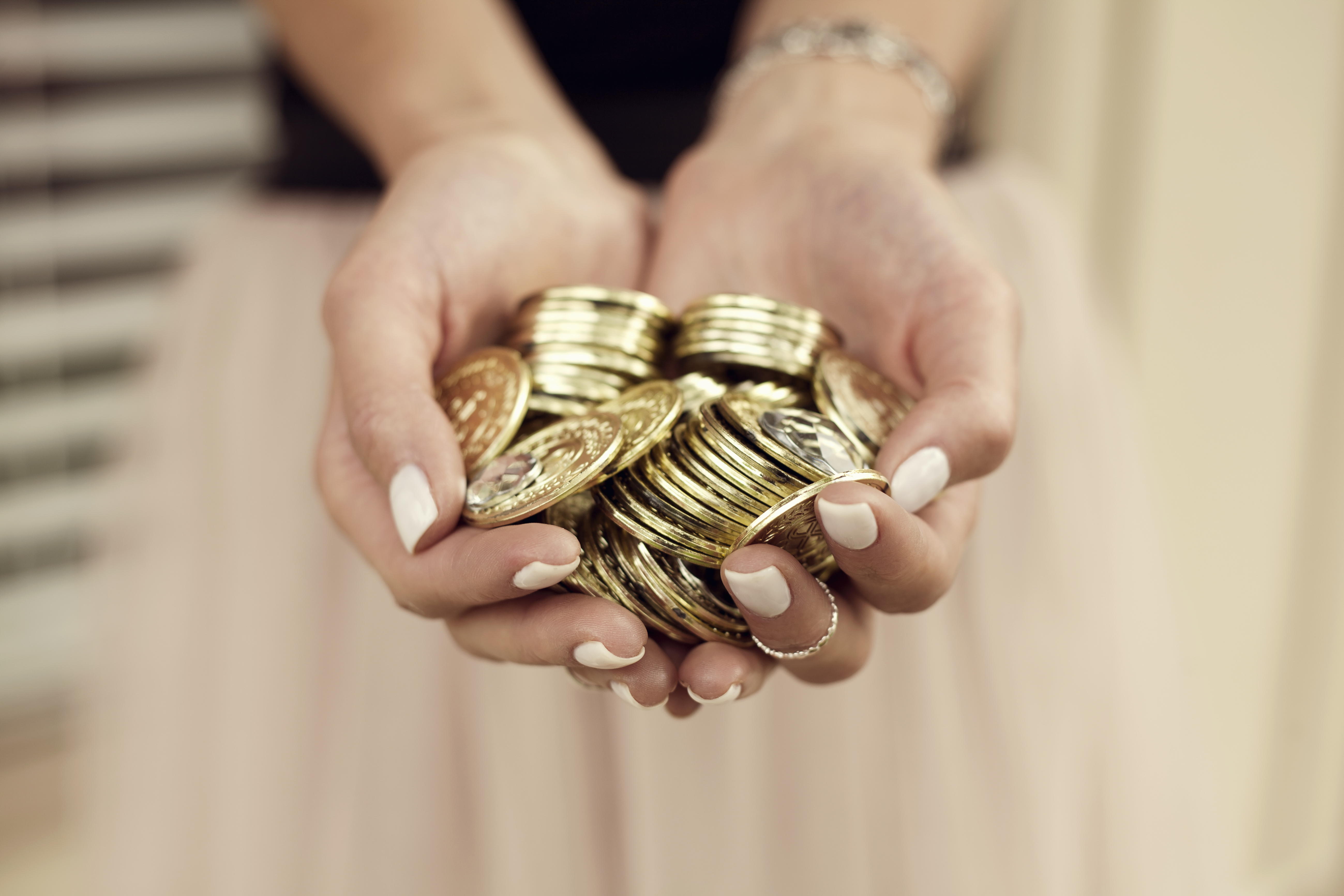 Young woman with handful of gold coins, focus on hands