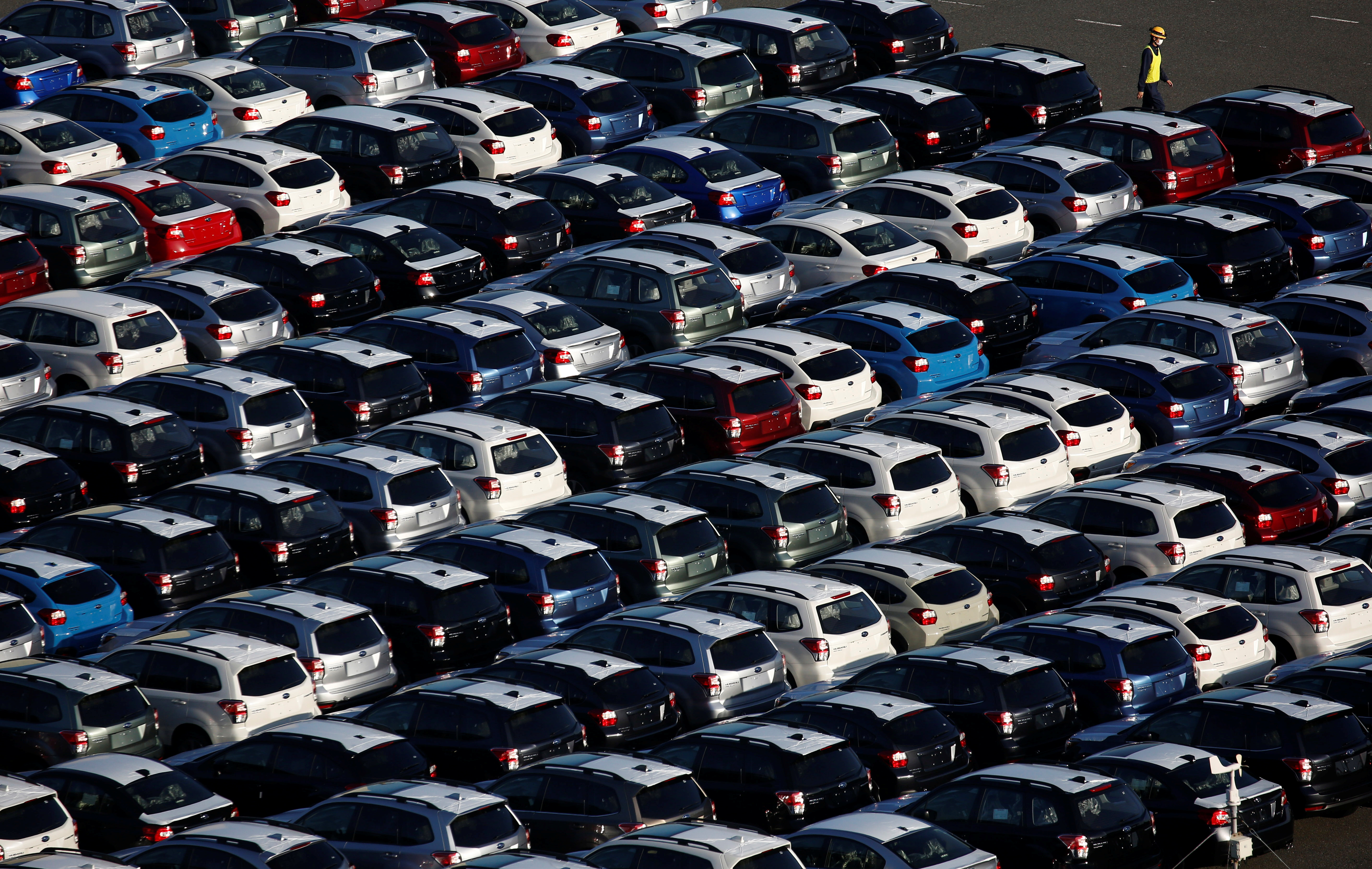 A worker walks past newly produced cars at an industrial port in Kawasaki