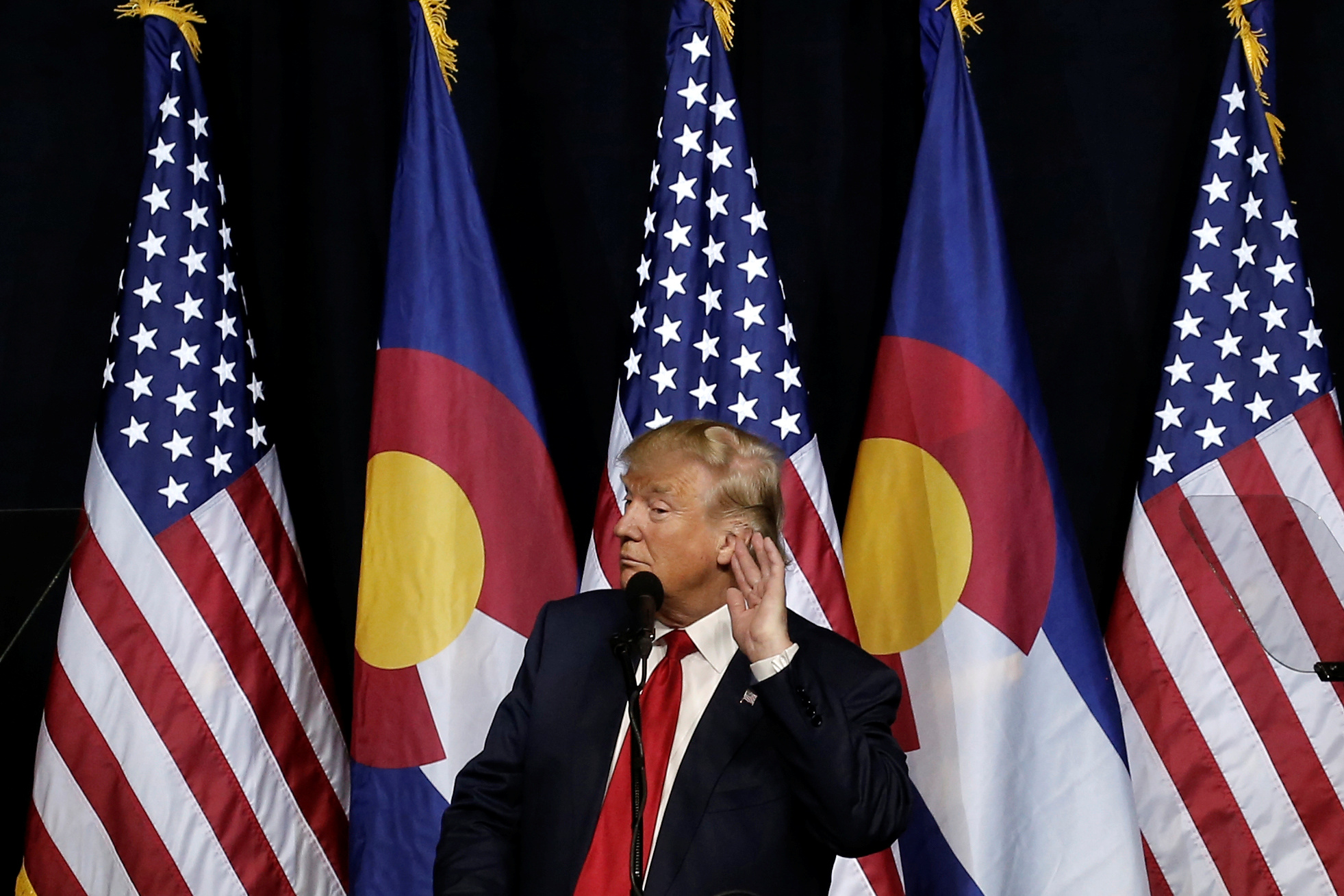 U.S. Republican presidential nominee Donald Trump puts his hand to his ear as he speaks at a campaign rally in Pueblo
