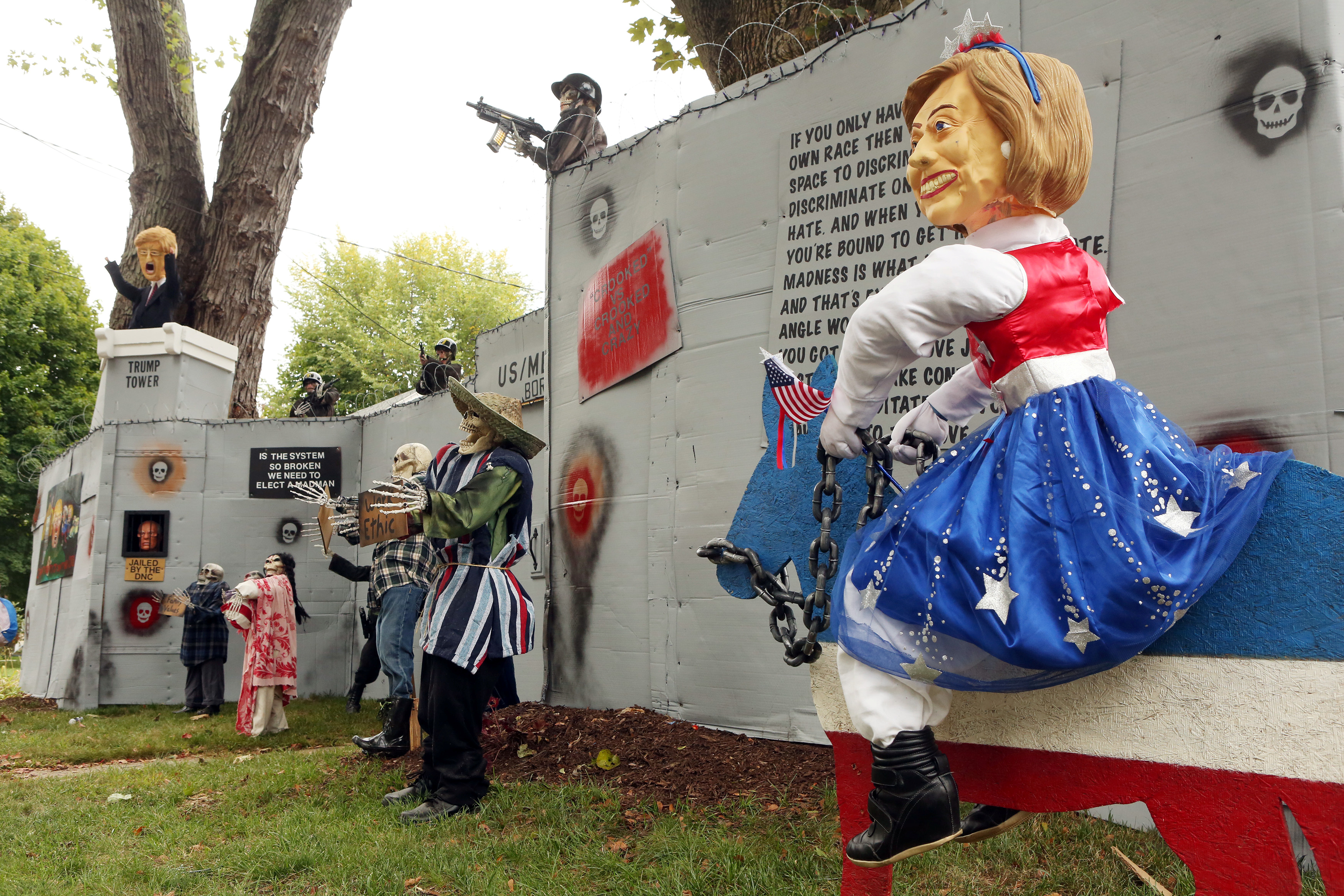 A Halloween display featuring a border wall and figures of Donald Trump, Hillary Clinton and Bernie Sanders is seen on the property of Matt Warshauer in West Hartford