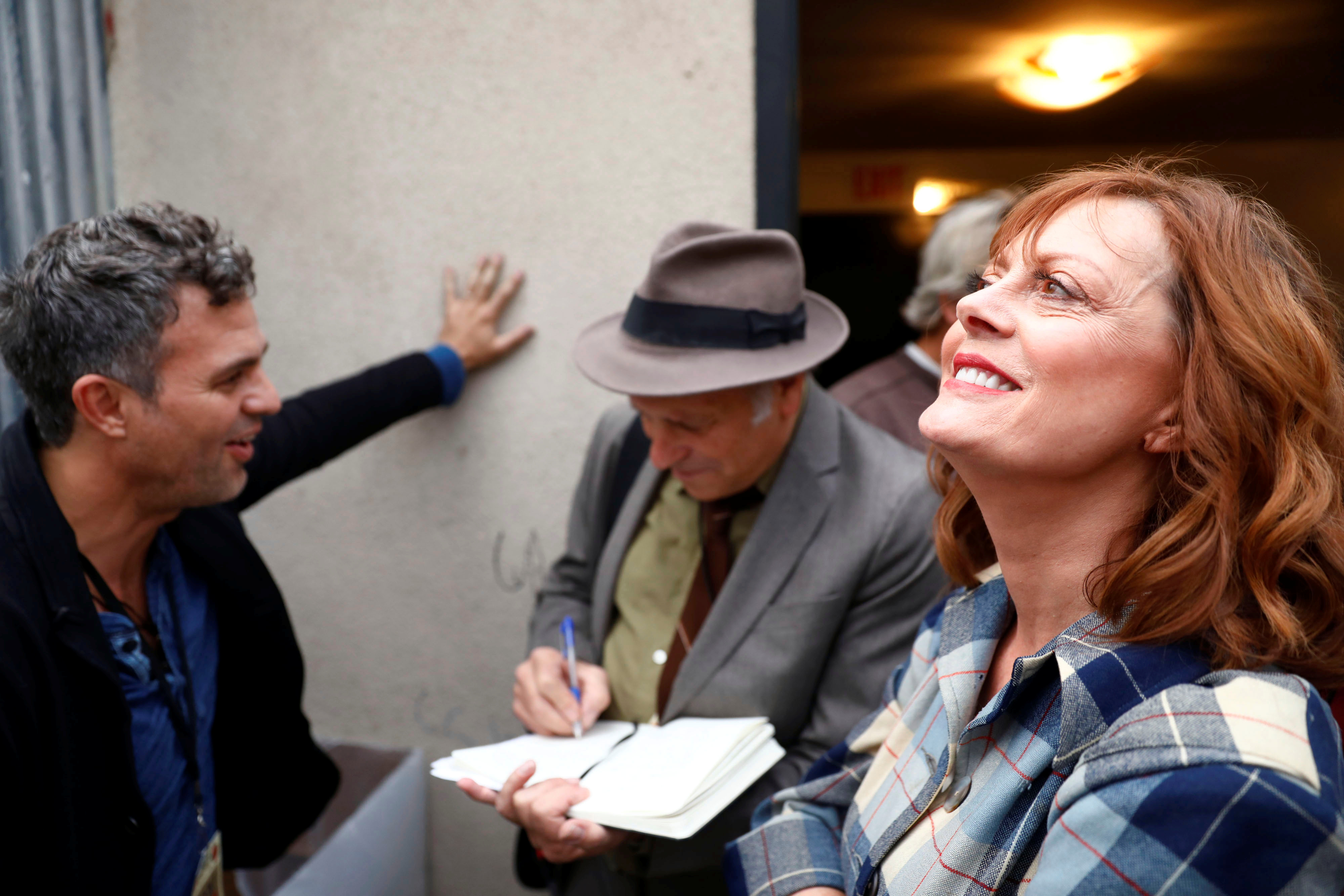 Actor Susan Sarandon smiles during an interview with author Greg Palast and Mark Ruffalo backstage at a climate change rally in solidarity with protests of the pipeline in North Dakota at MacArthur Park in Los Angeles, California