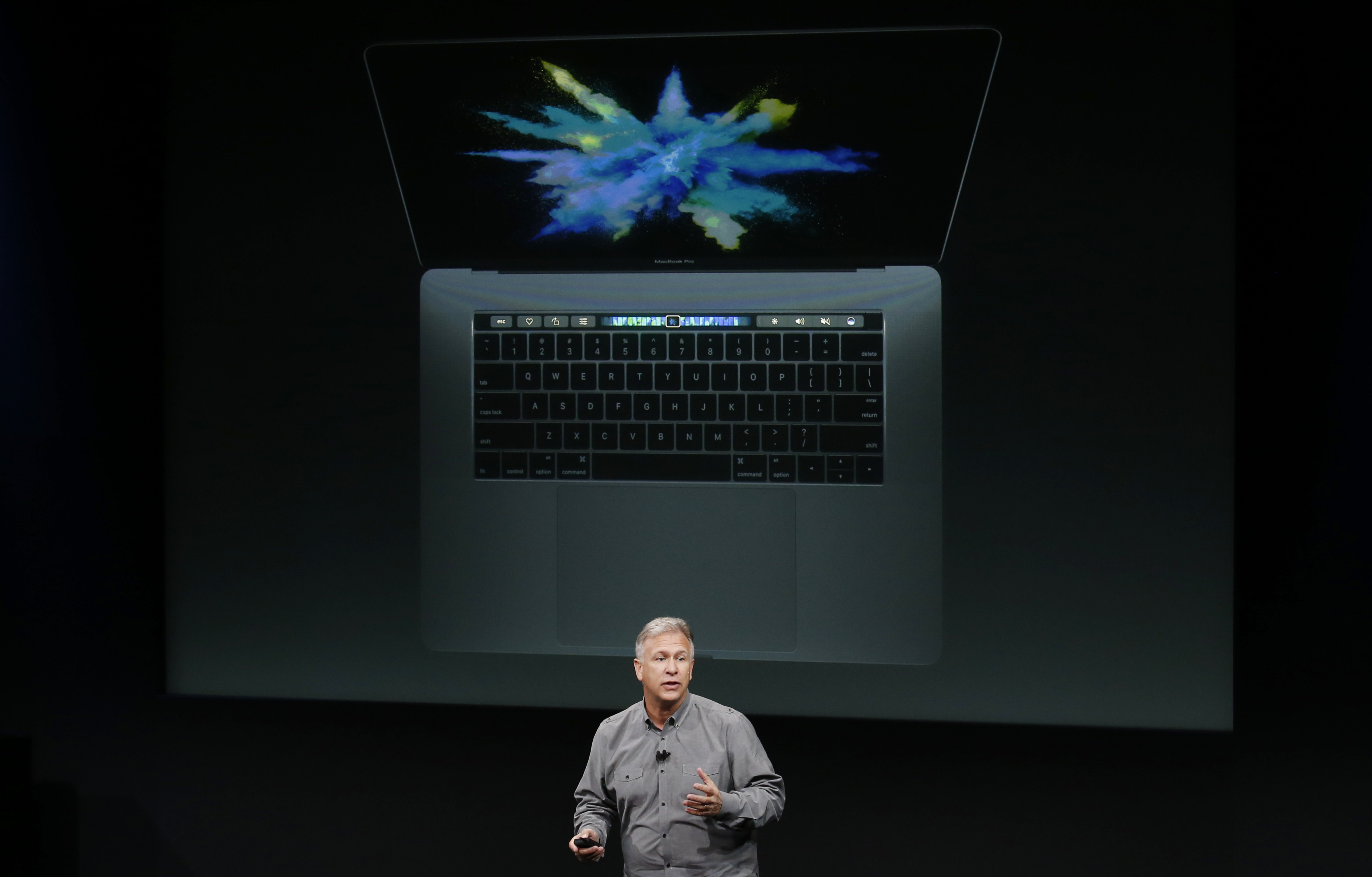 Phil Schiller, senior vice president of worldwide marketing at Apple, speaks under a graphic of a new MacBook Pro during an Apple media event in Cupertino