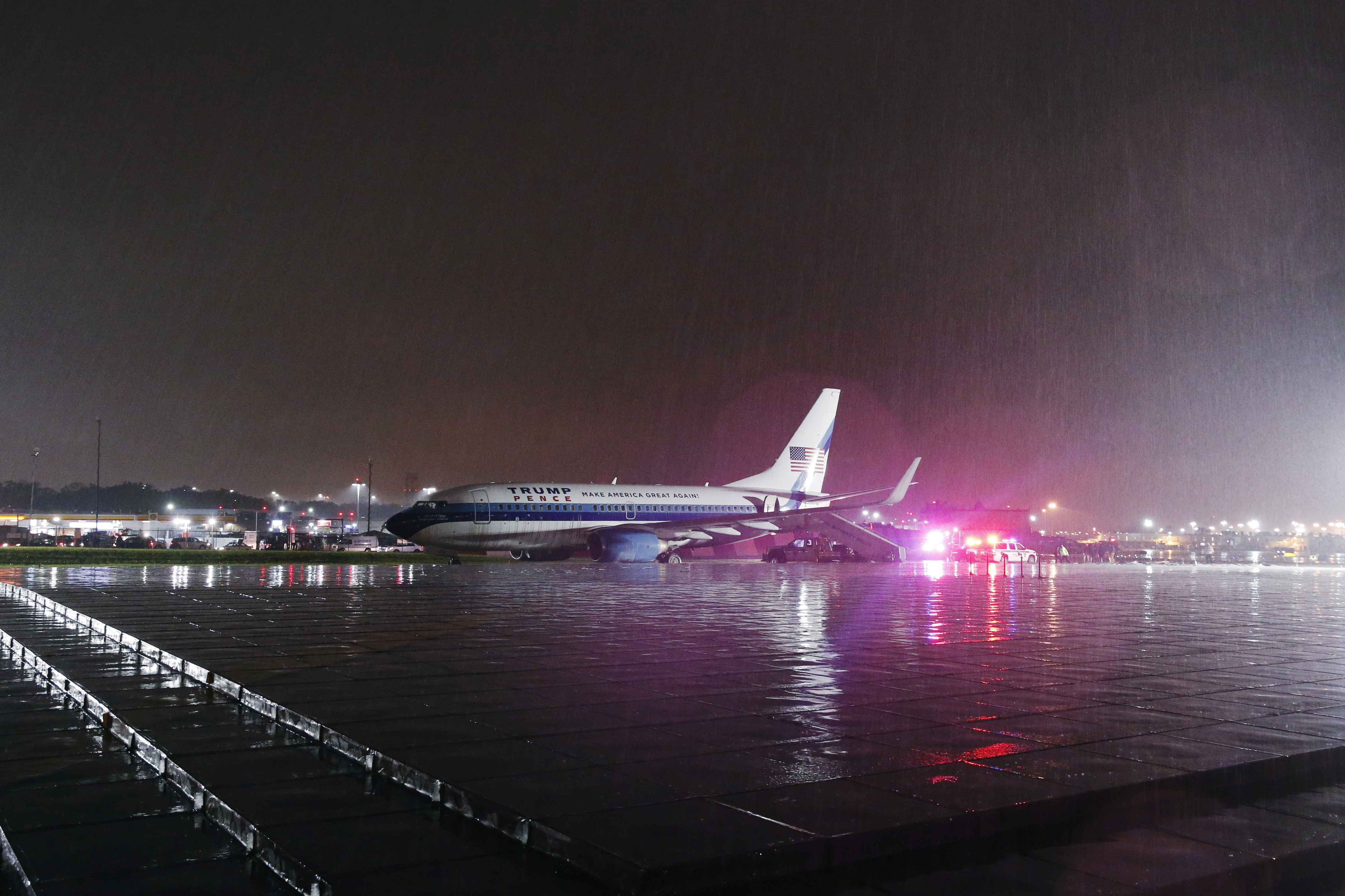 A campaign plane that had been carrying Mike Pence rests in the grass after it skidded off the runway while landing in the rain at LaGuardia Airport in New York