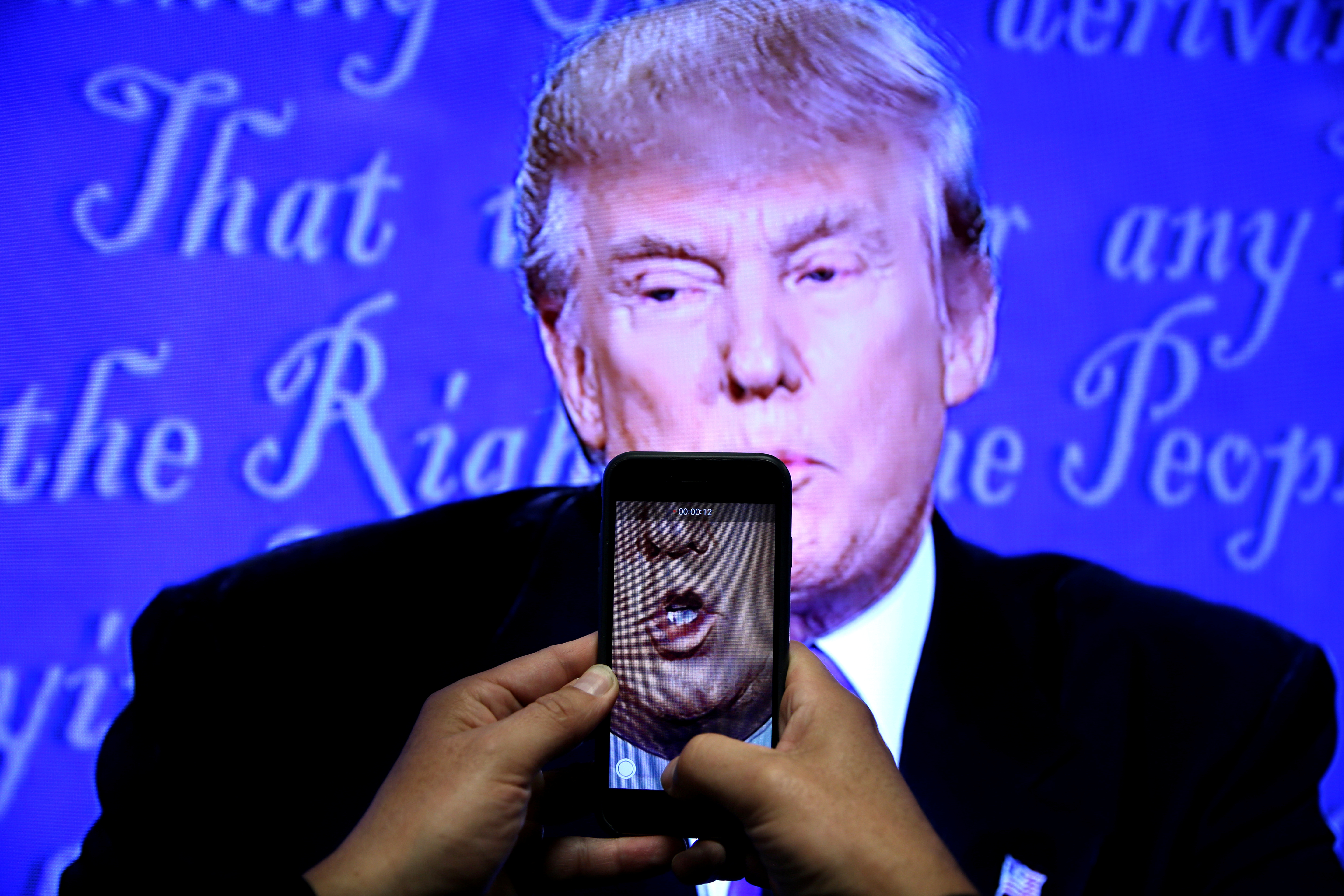 A journalist records a video from screen as Republican U.S. presidential nominee Donald Trump speaks during the first presidential debate with U.S. Democratic presidential candidate Hillary Clinton at Hofstra University in Hempstead