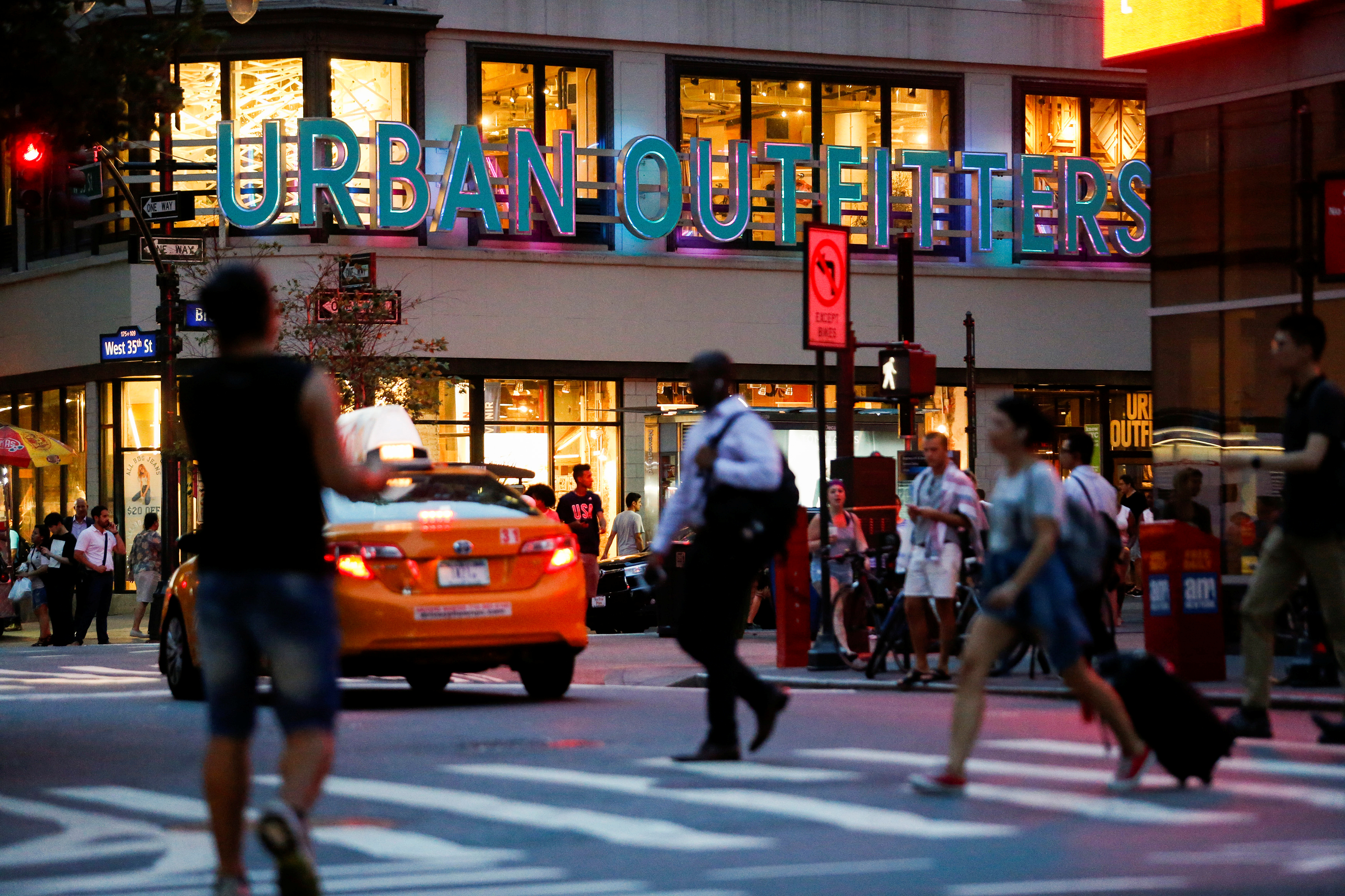 People crosses the street next to the Urban Outfitters store in Manhattan, New York, U.S., August 15, 2016.