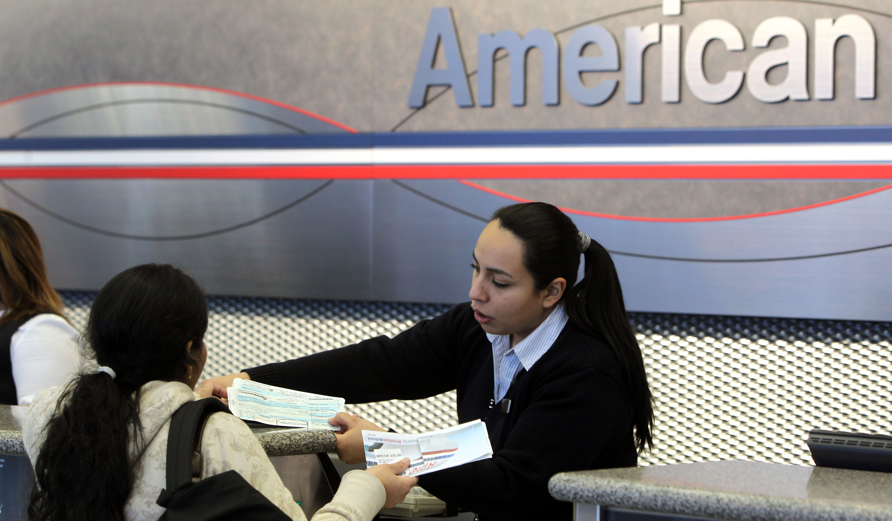 A ticket agent at the American Airlines terminal at O'Hare International Airport in Chicago, Illinois, discusses a ticket with a customer.
