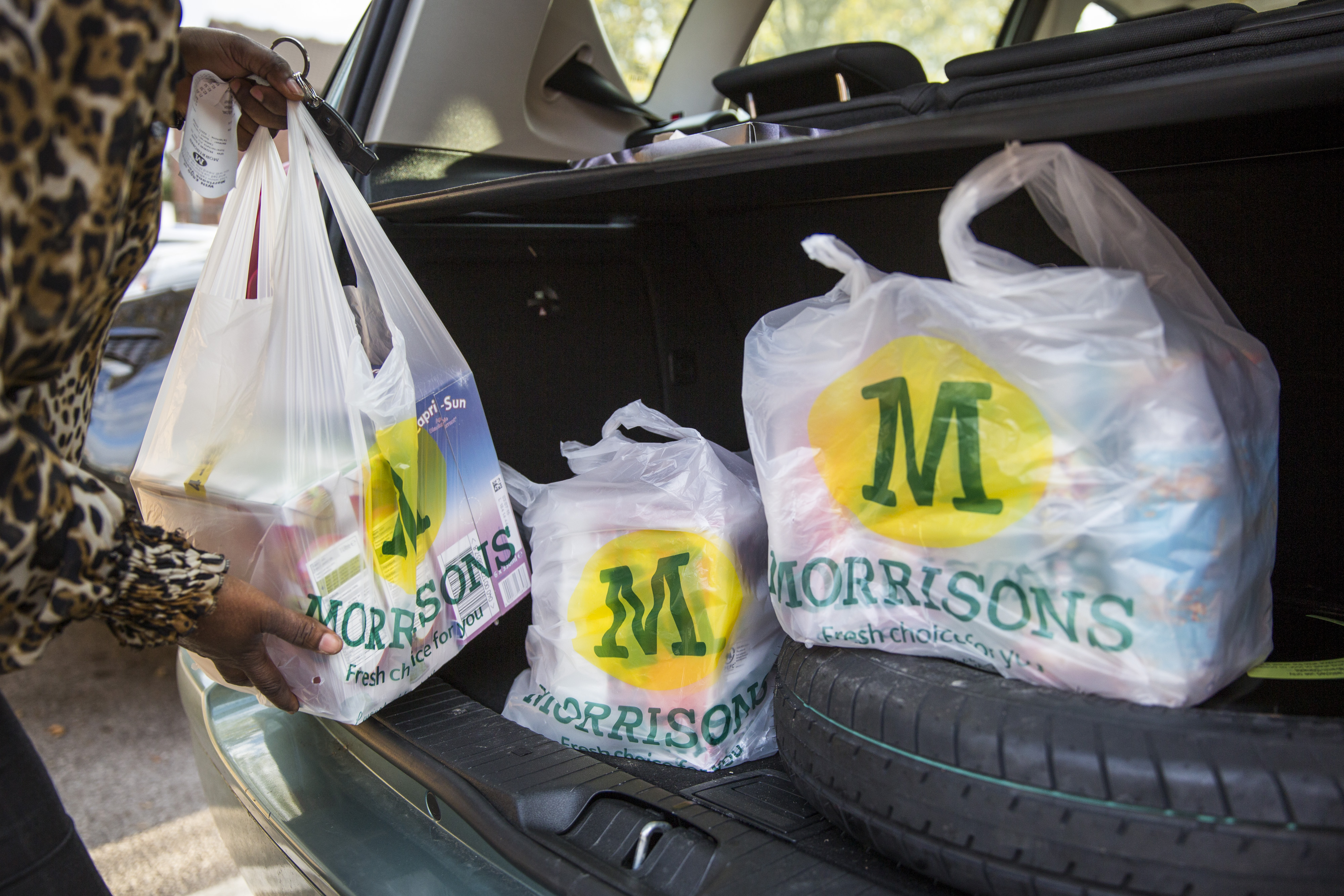 A customer places Morrison's shopping bags in their car in London.