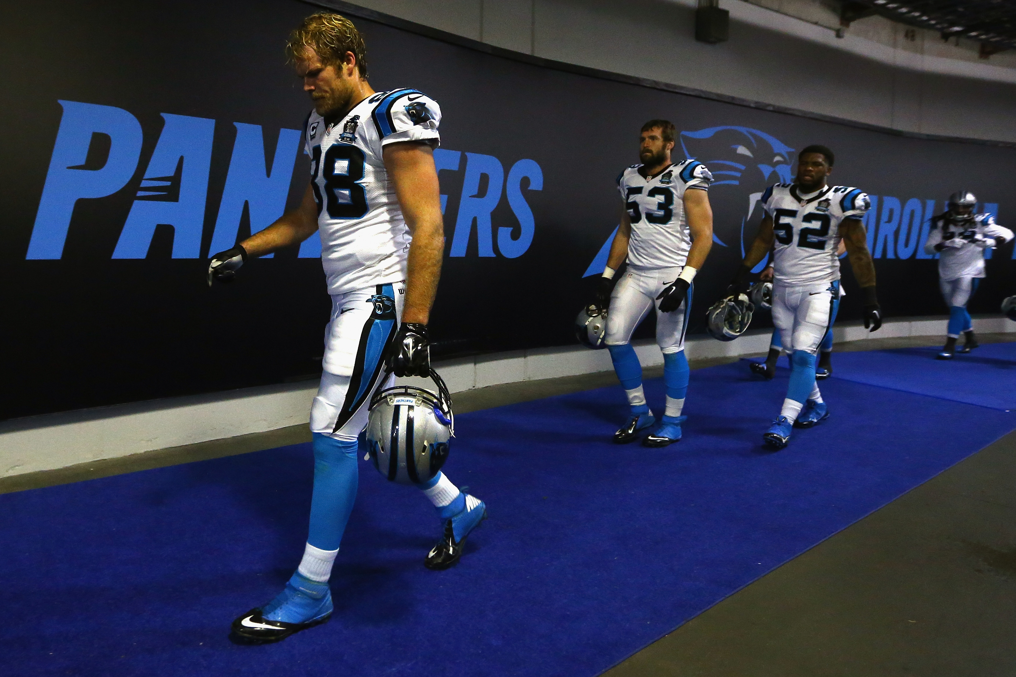 Greg Olsen #88, Ben Jacobs #53, and Kevin Reddick #52 of the Carolina Panthers return to the locker room at Bank of America Stadium.