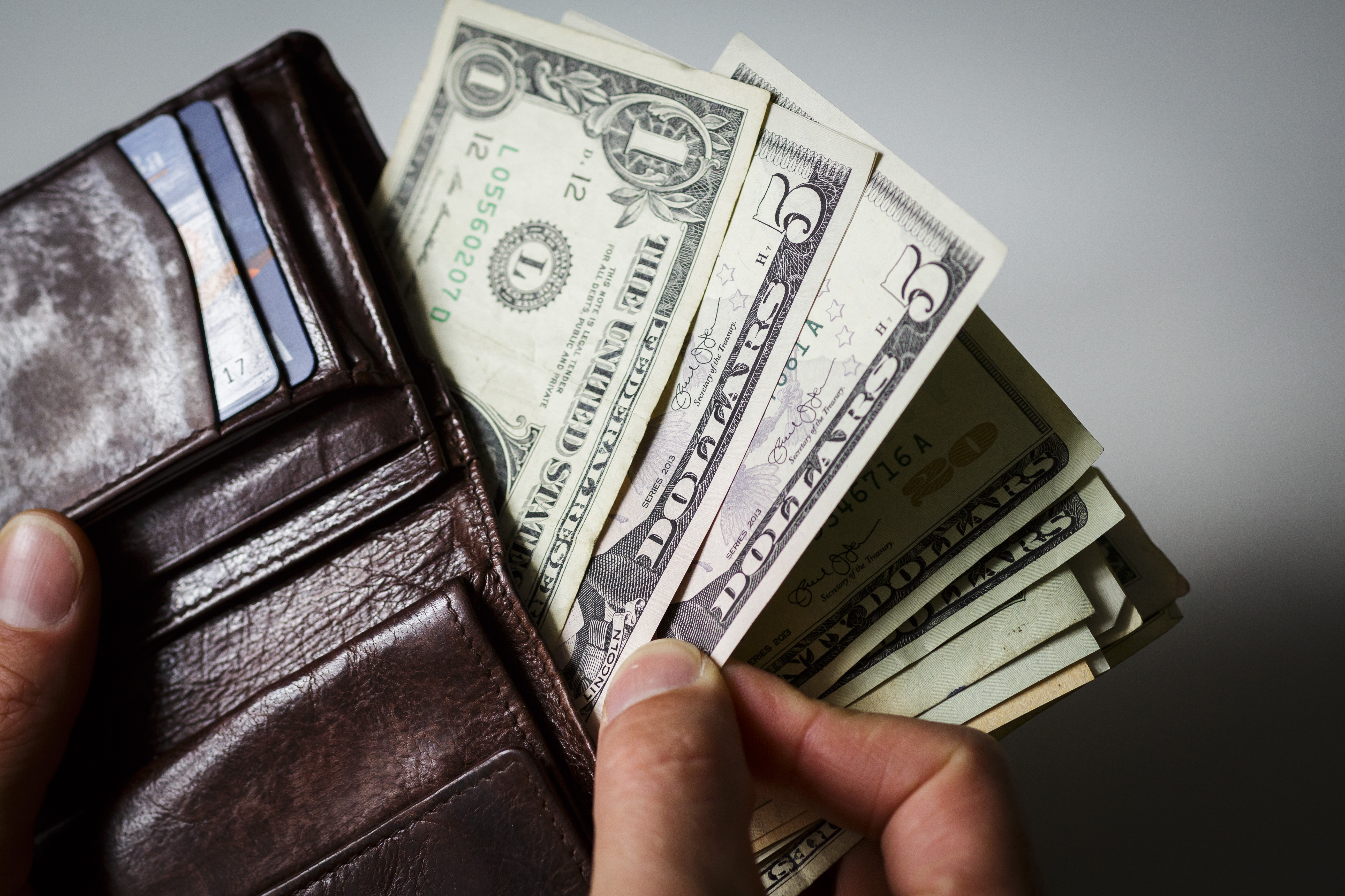 A man hold a wallet, filled with dollar bills.