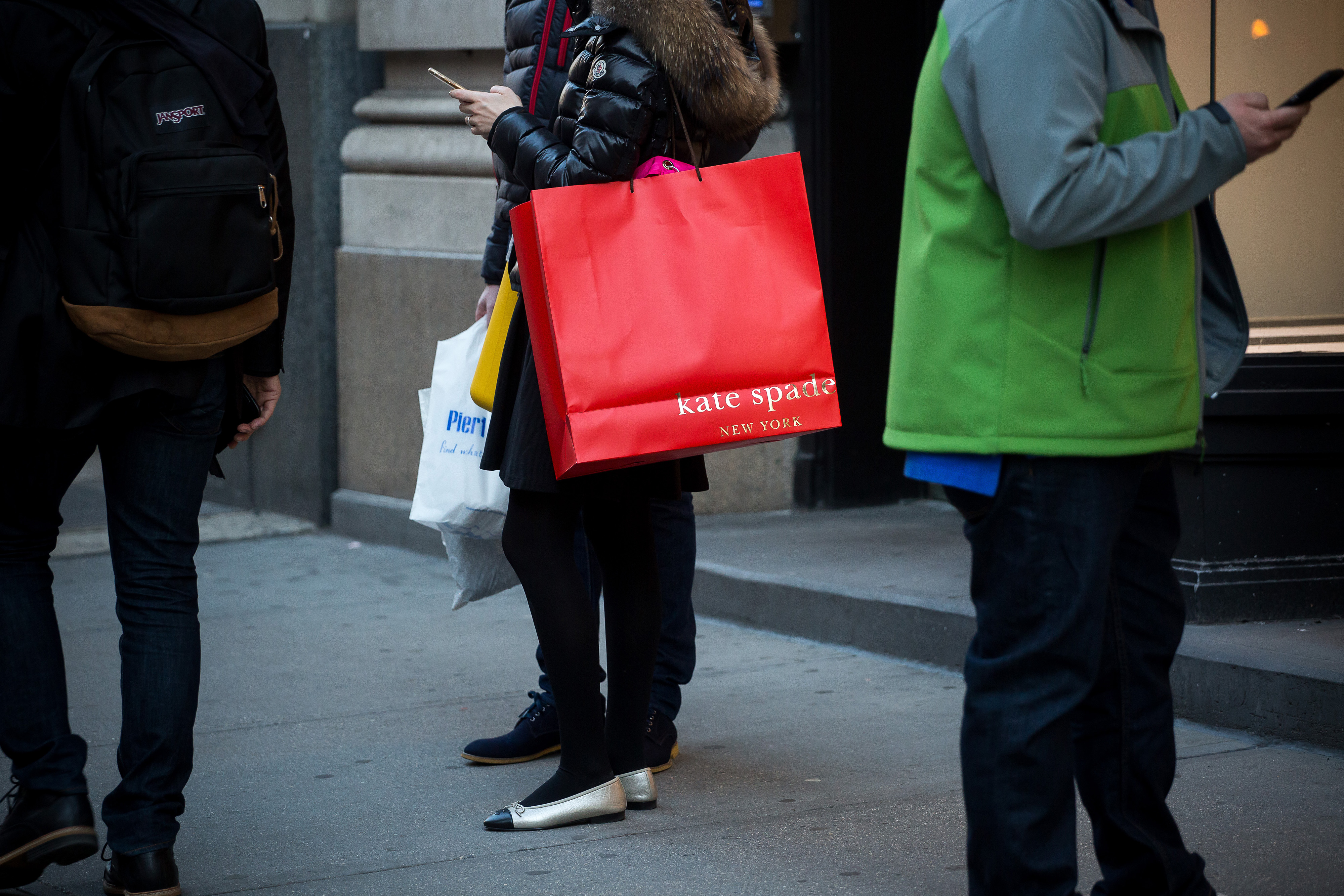 A shopper carries a Kate Spade & Co. bag outside a store in New York, U.S., on Sunday, Feb. 28, 2016.