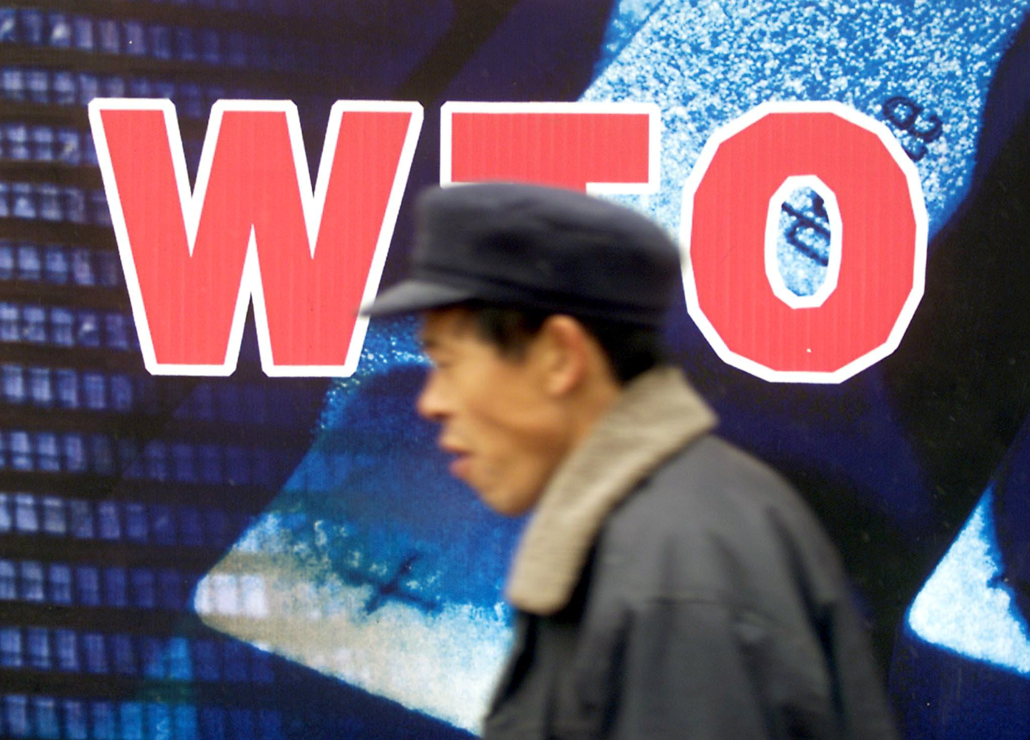 A Chinese man walks past a billboard welcoming the