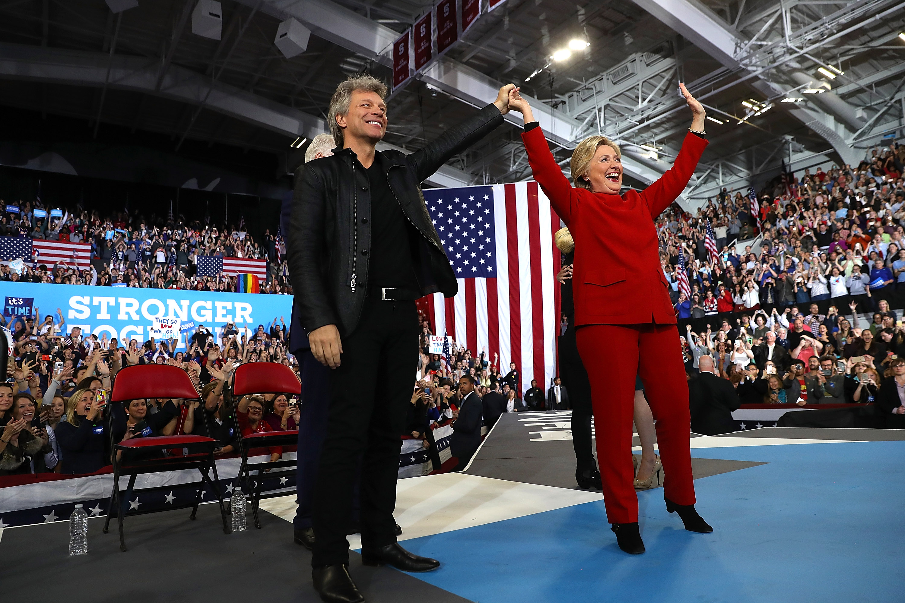 Democratic presidential nominee Hillary Clinton (R) with musician Jon Bon Jovi during a campaign rally on November 8, 2016.