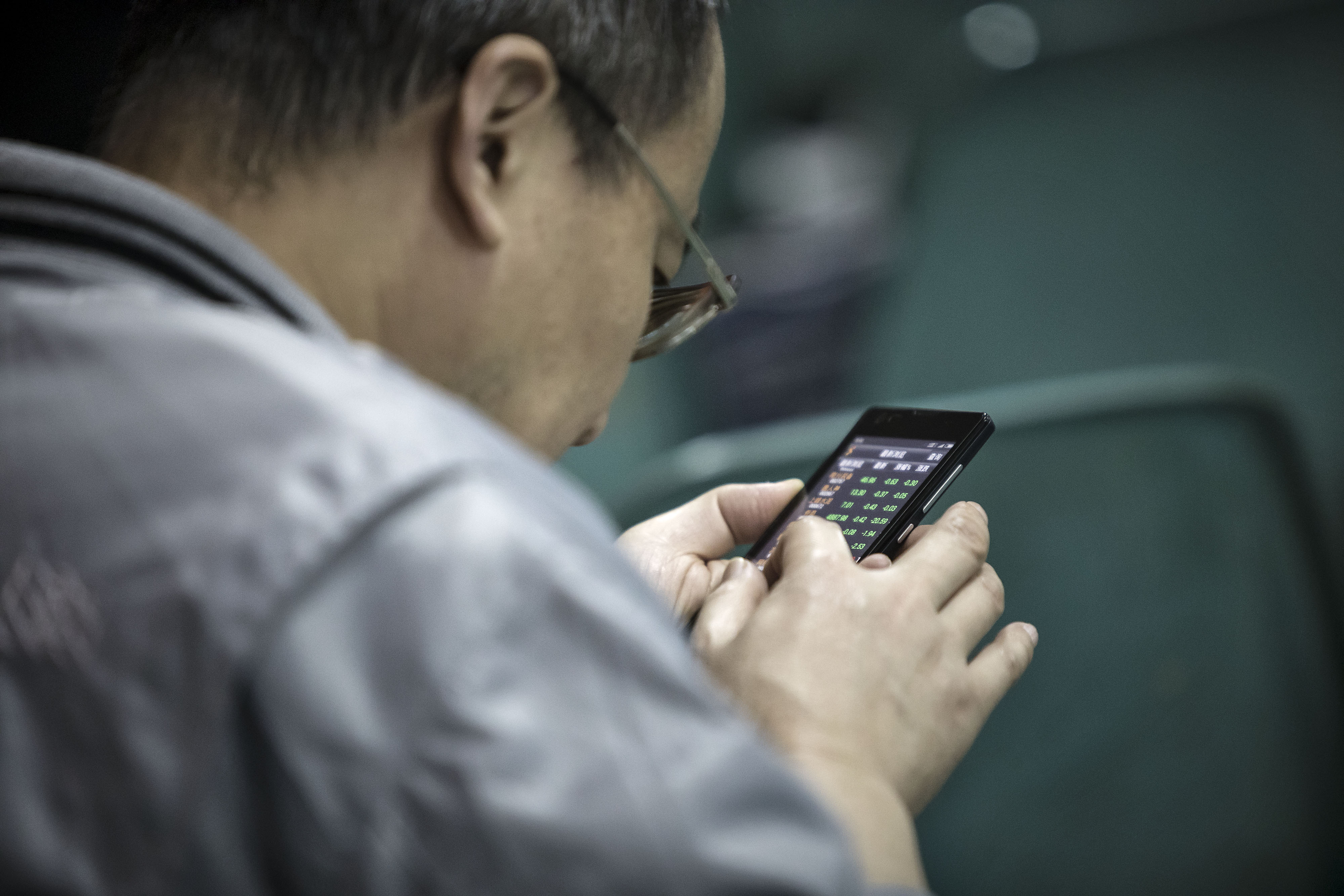 A man looks at share prices on a smartphone at a securities brokerage in Shanghai, China, on Wednesday, Nov. 9, 2016.