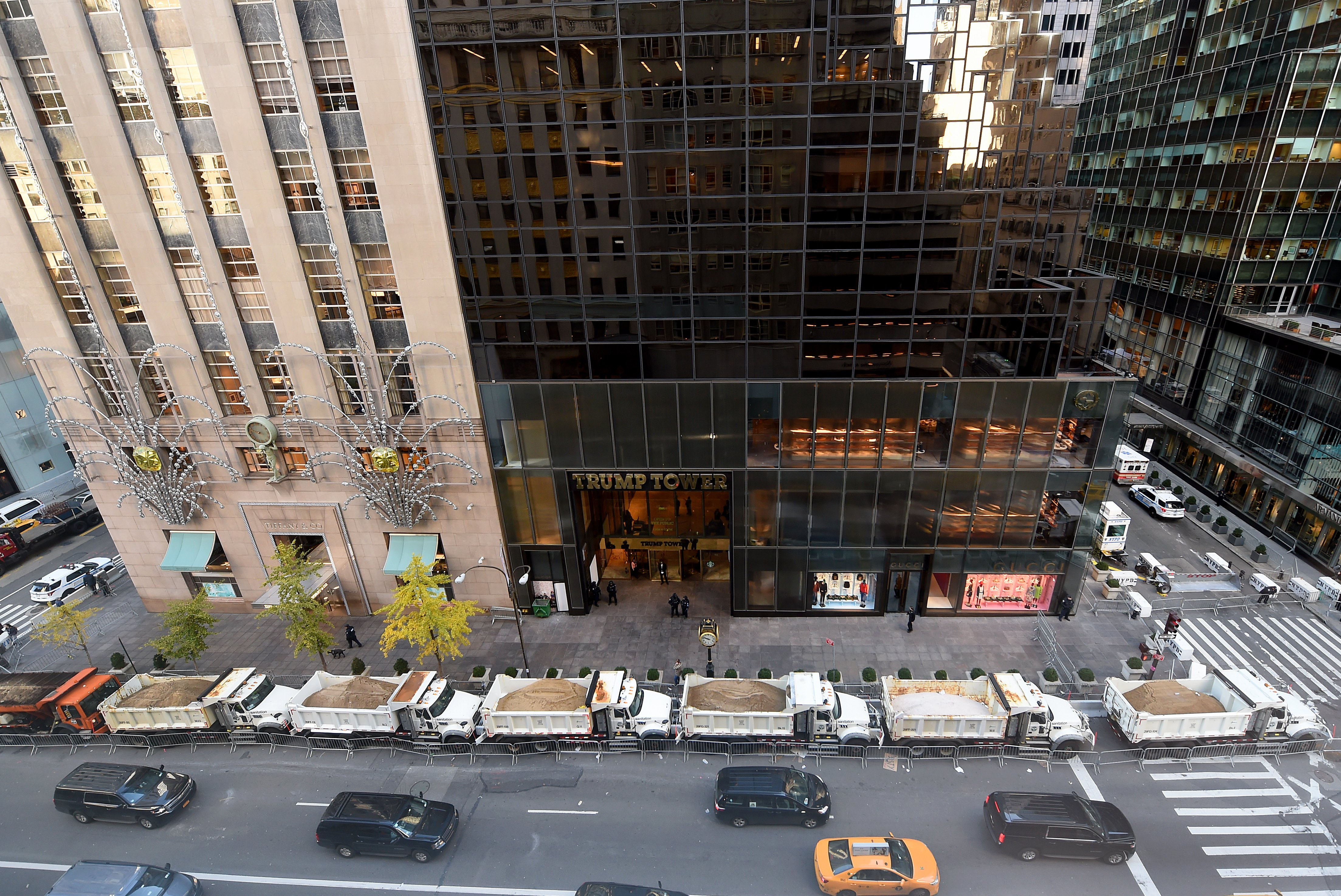 A protective barrier of Sanitation Department trucks are parked in front of Trump Tower on 5th Avenue in New York City.