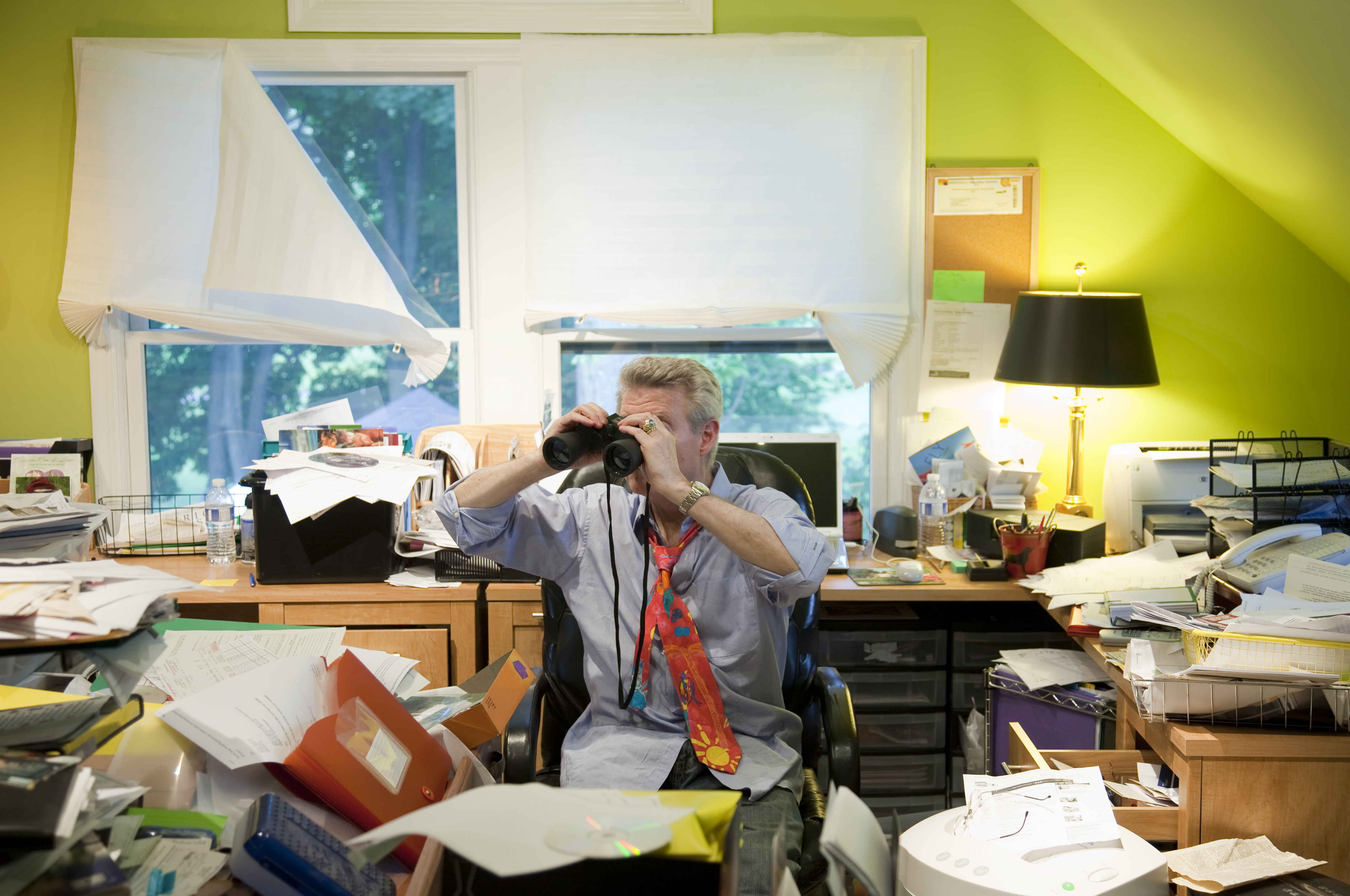 Baby Boomer w/ Binoculars in Messy Office