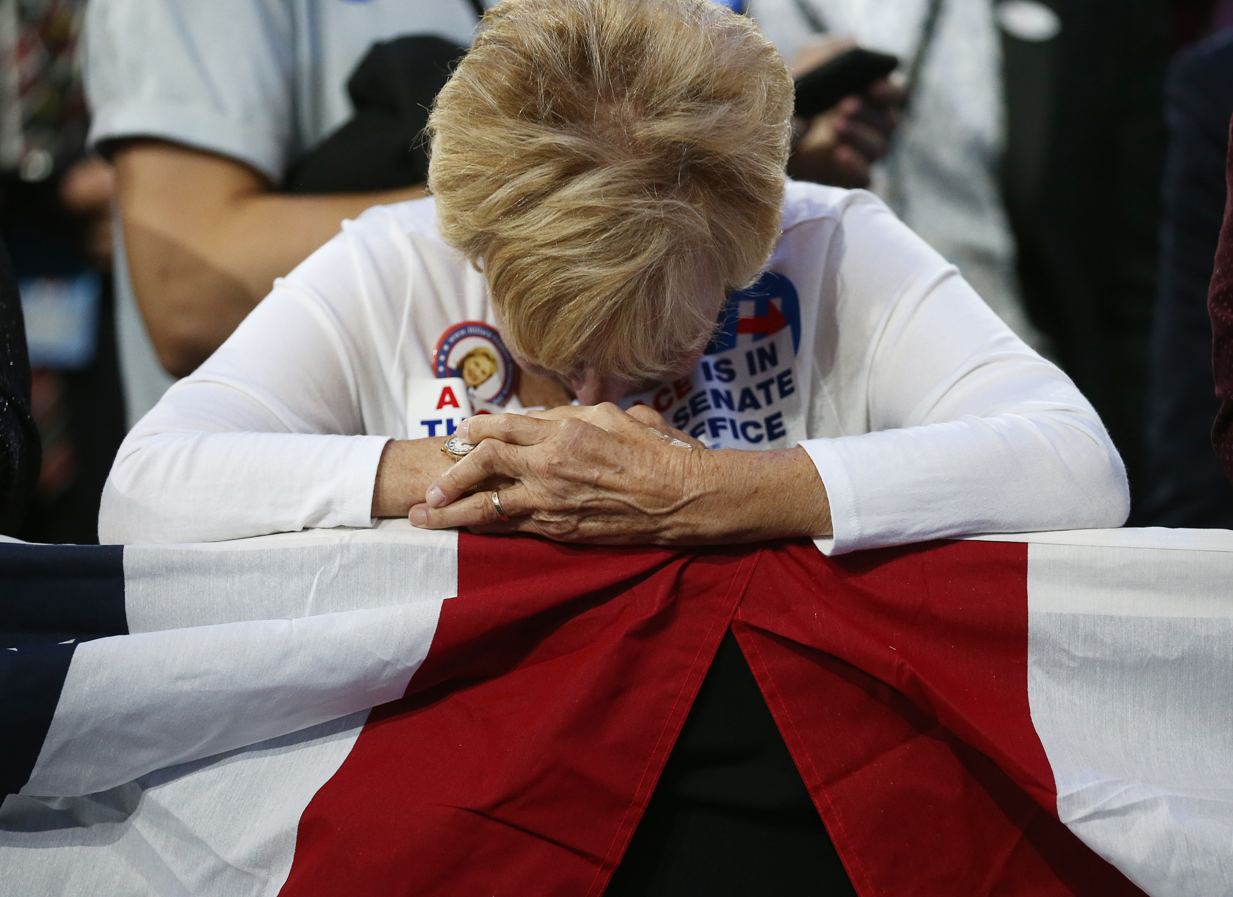 Supporter of Democratic presidential nominee Hillary Clinton watbows head at her rally in New York