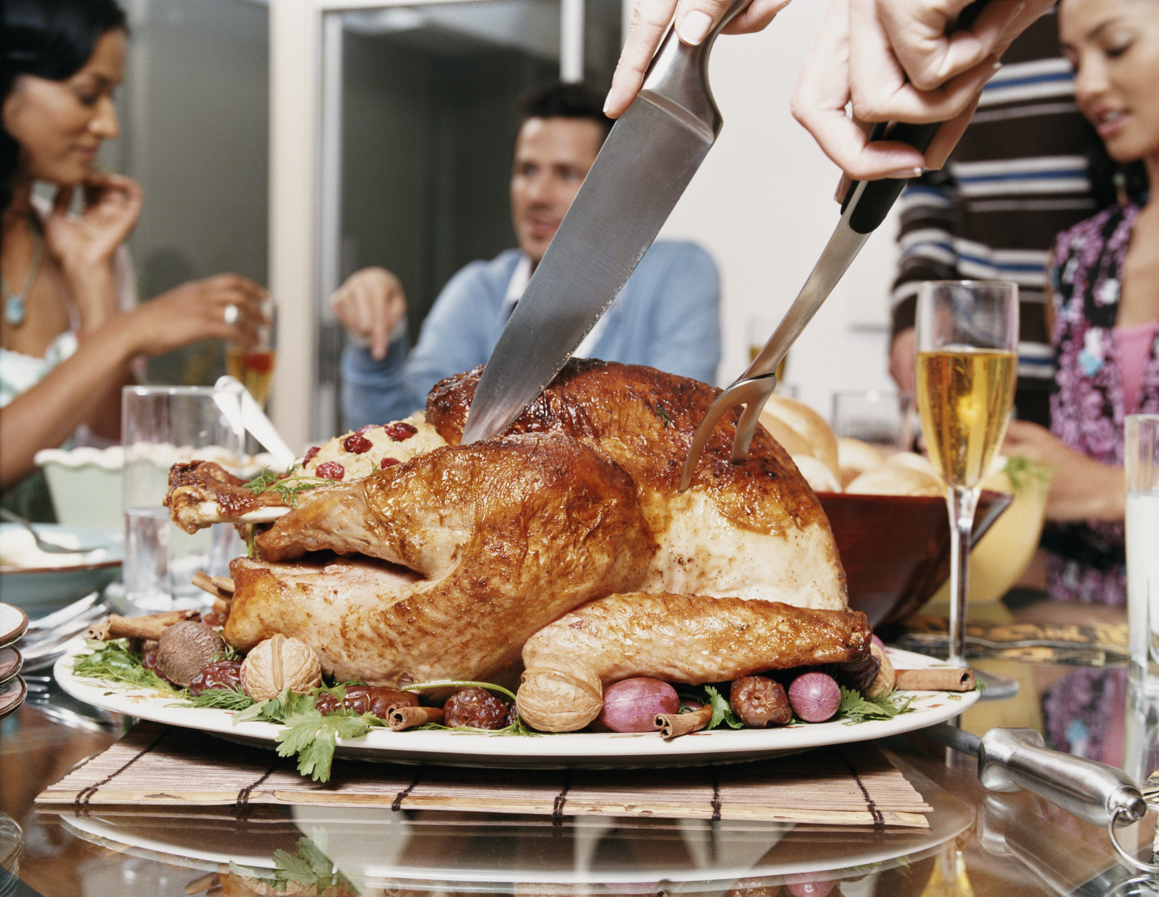 Small Group of Friends Sit Round a Dining Table While a Thanksgiving Turkey is Cut