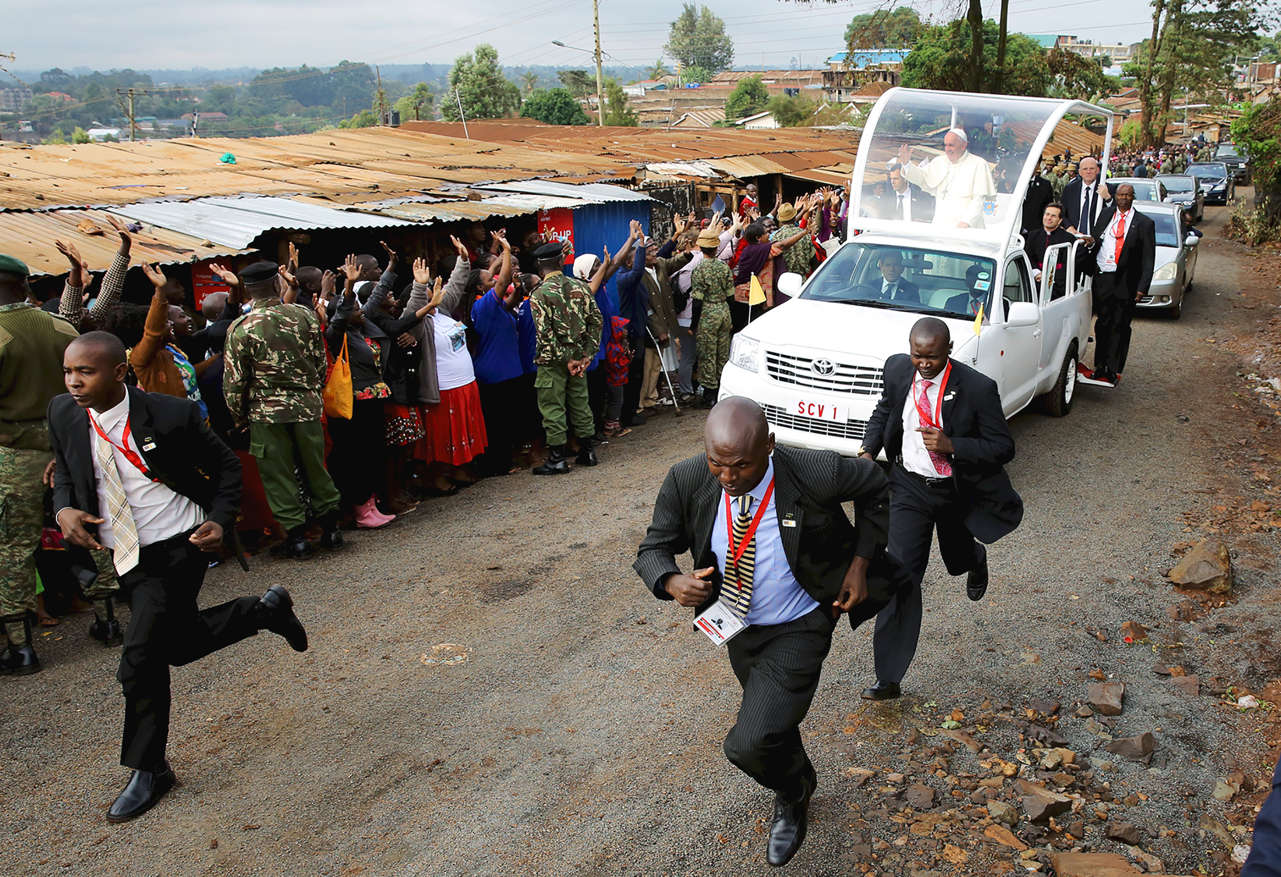 Pope Francis waves as he arrives at the Kangemi slums on the outskirts of Kenya's capital Nairobi