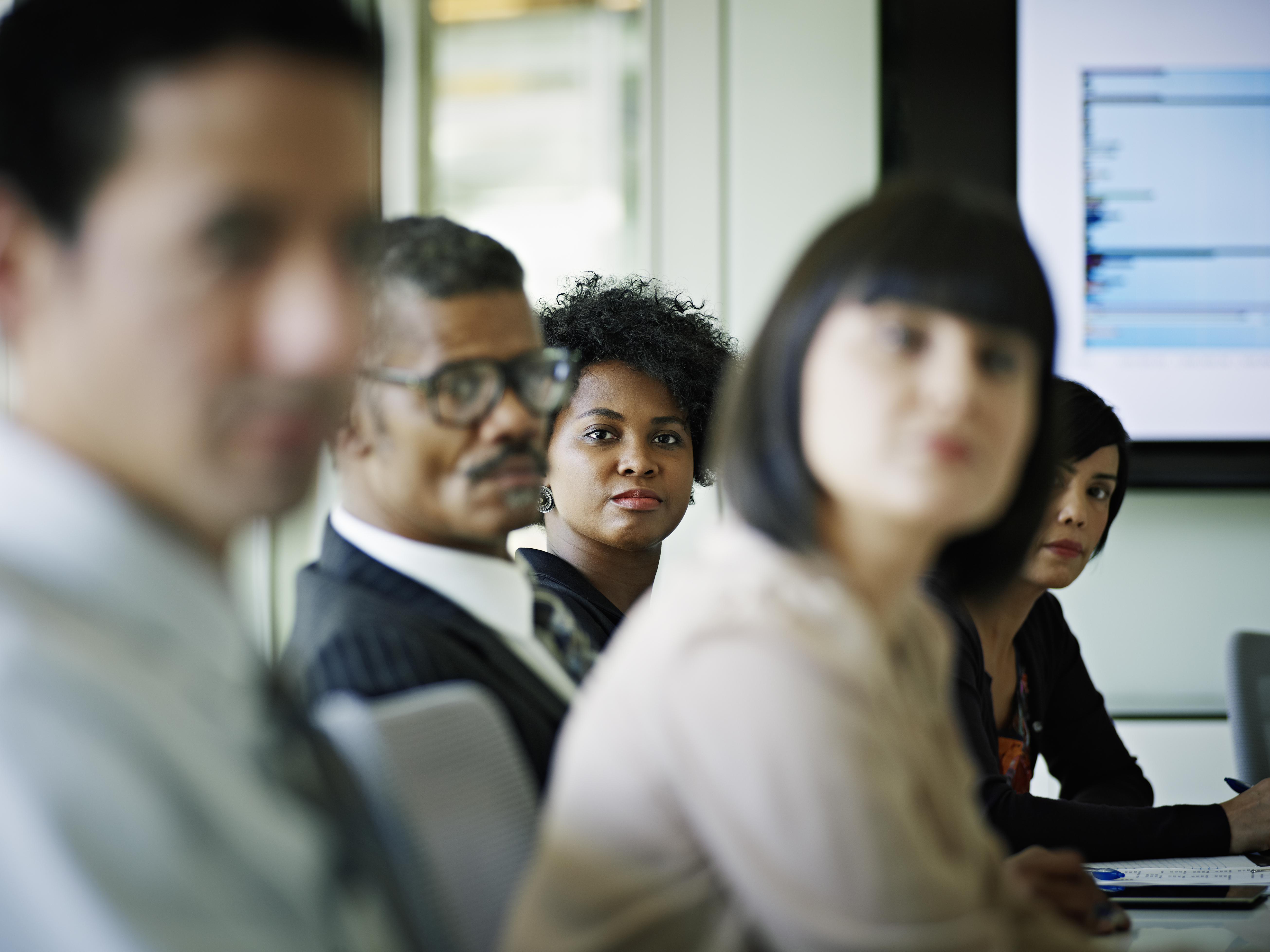 Businesswoman sitting surrounded by coworkers