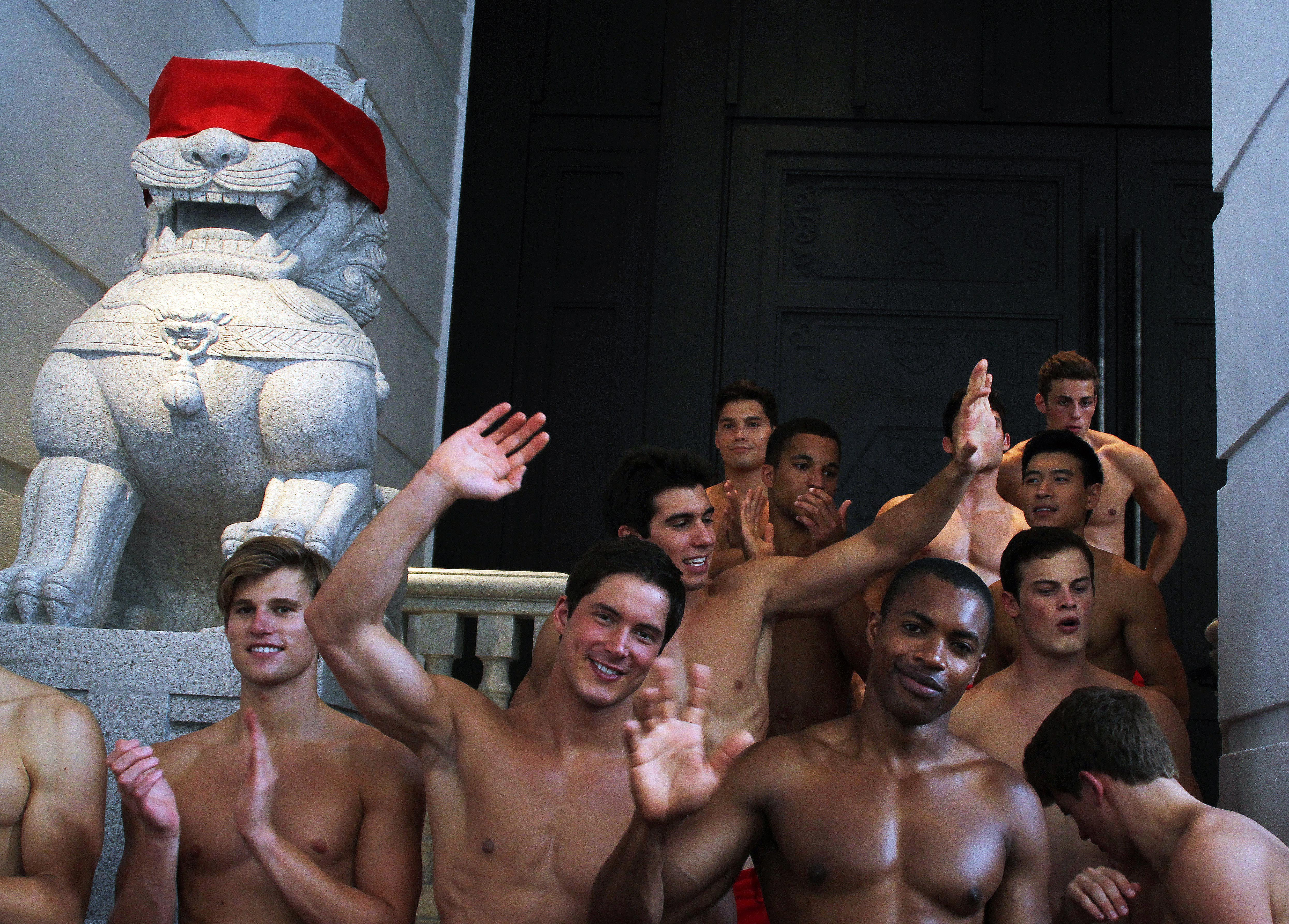 A group of topless male models waves to