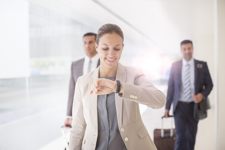 Businesswoman checking wristwatch in corridor