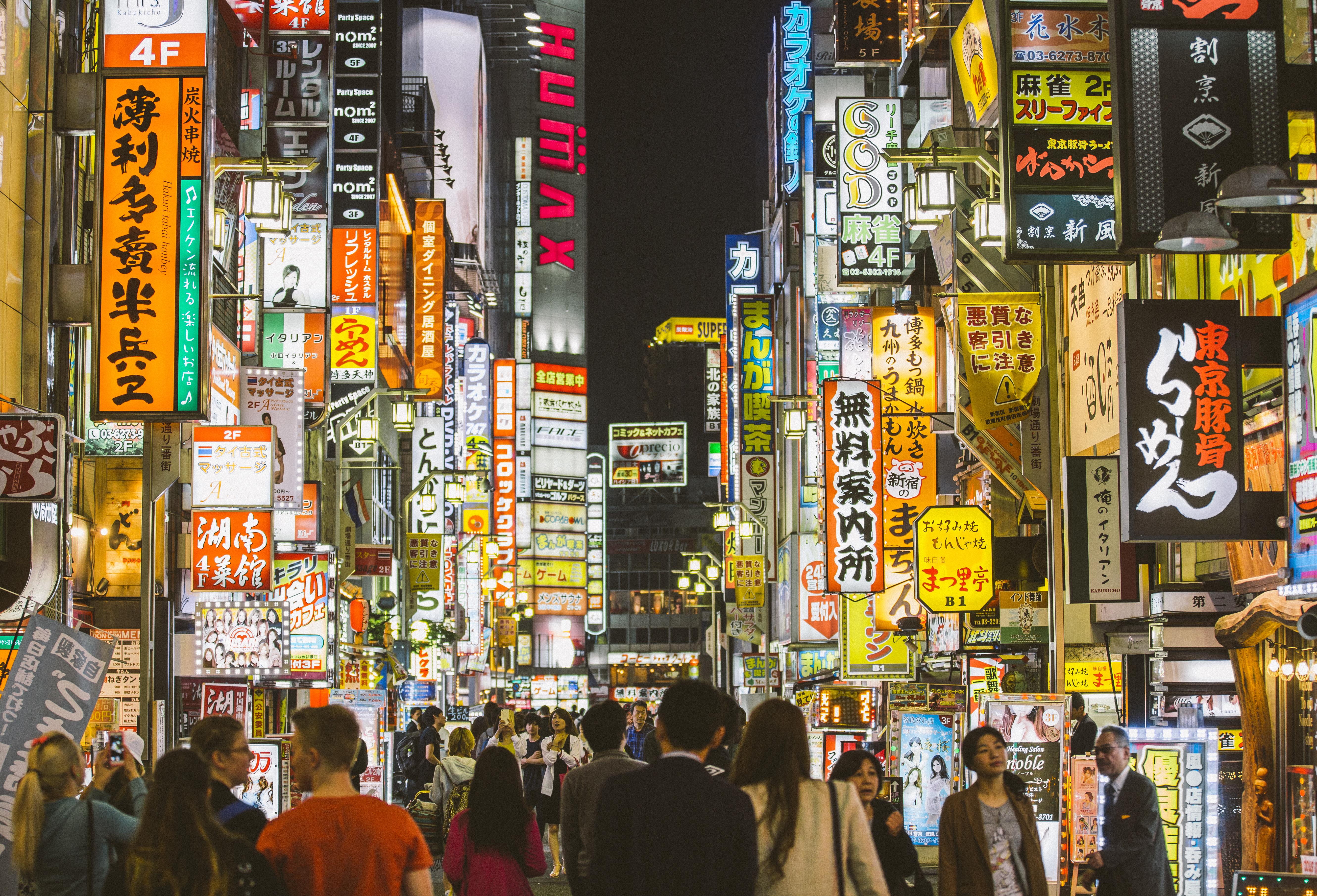 People walking among neon sign in Shinjuku, Tokyo