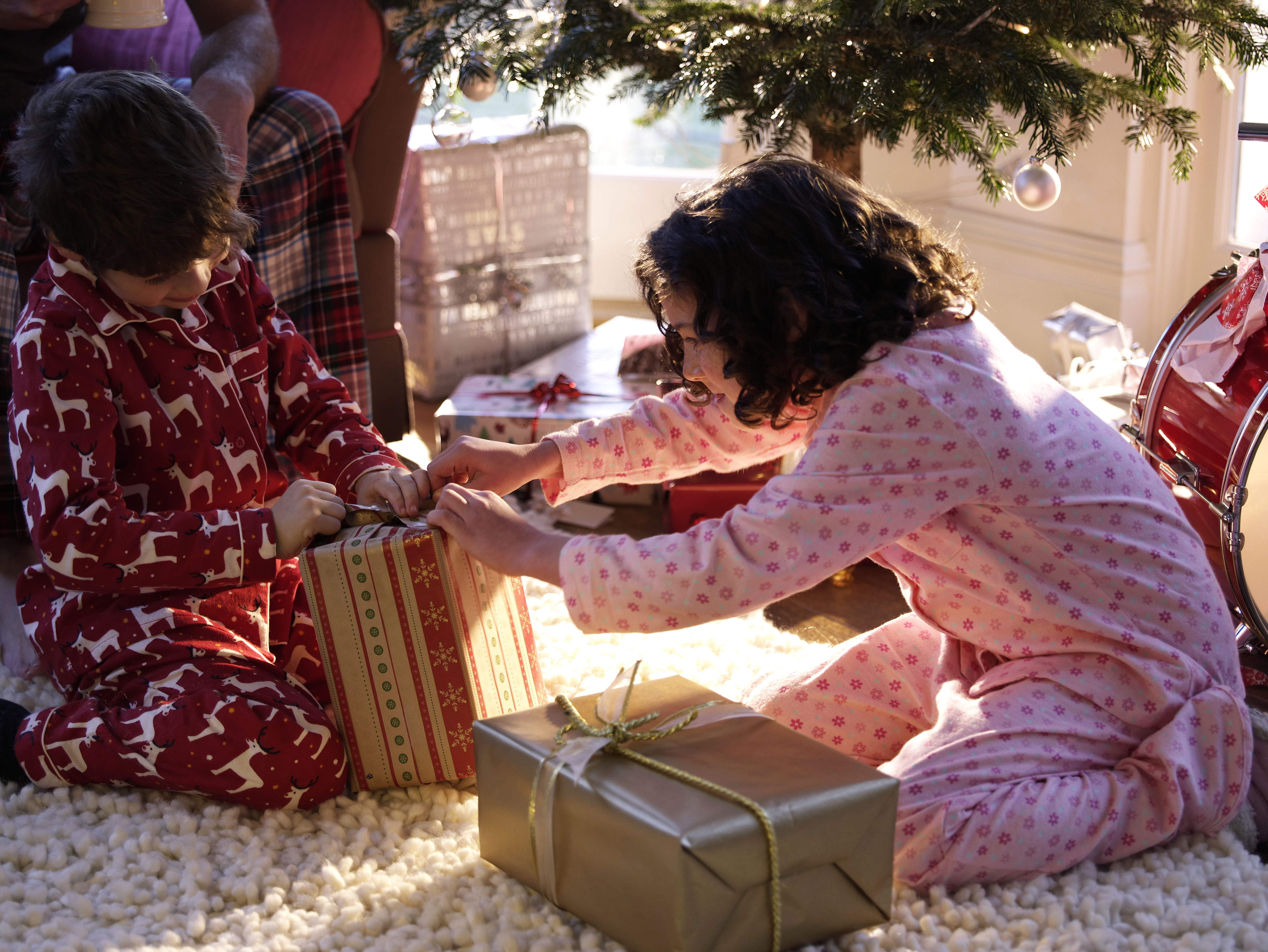 Brother and sister (6-11) unwrapping Christmas gifts