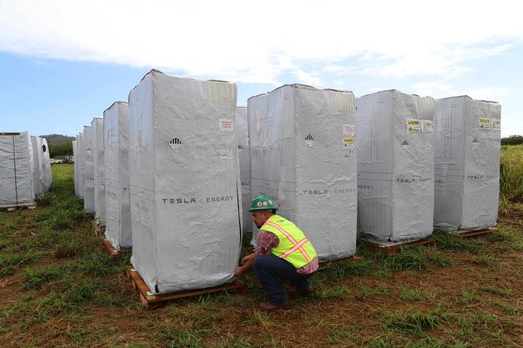 Tesla batteries await installation at a solar panel farm built by SolarCity for Kauai Island Utility Cooperative on the Hawaiian island of Kauai. SolarCity Senior Commercial Project Manager Danny Valdez unzips the battery's cover.