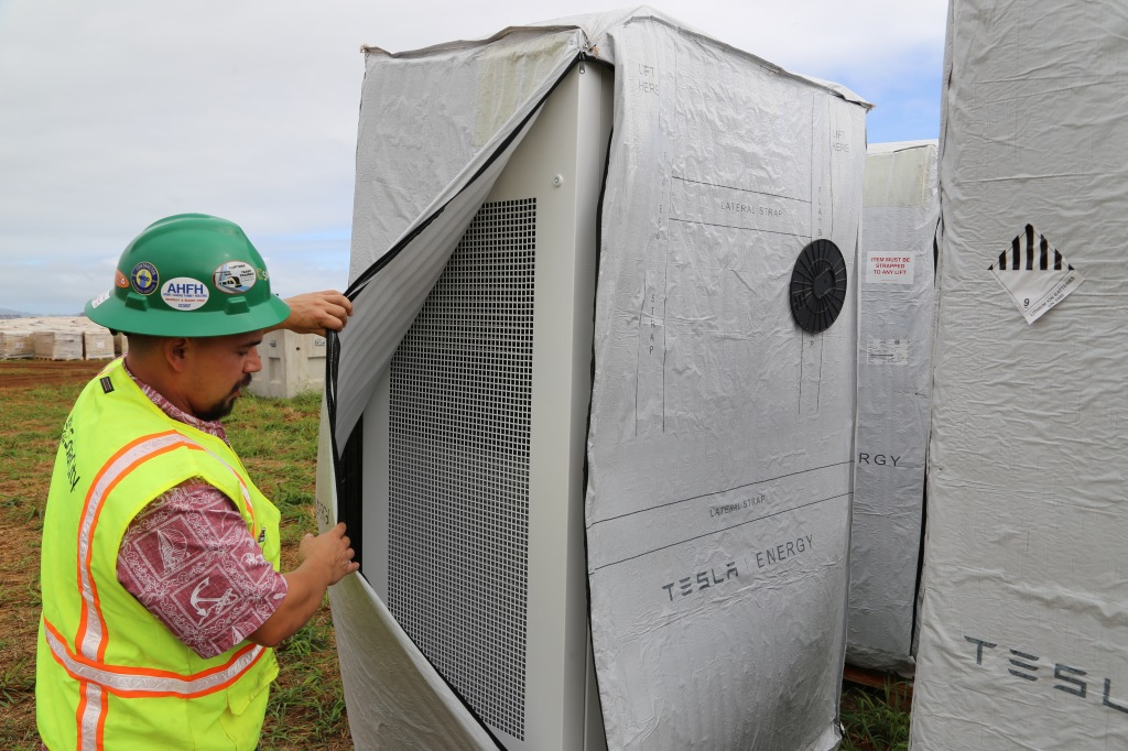 SolarCity's Senior Commercial Project Manager, Danny Valdez, checks out one of Tesla's Powerwalls at a solar farm on the island of Kauai.