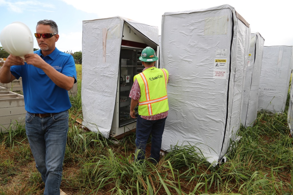 Kauai Island Utility Cooperative's Engineering Manager John Cox (L) and SolarCity's Senior Commercial Project Manager Danny Valdez (R) check out a Tesla inverter for a new solar and battery system.