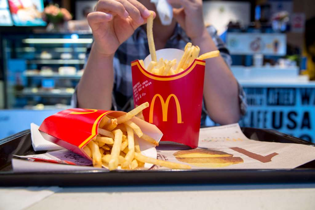 A girl eats fried chips in a McDonald's restaurant