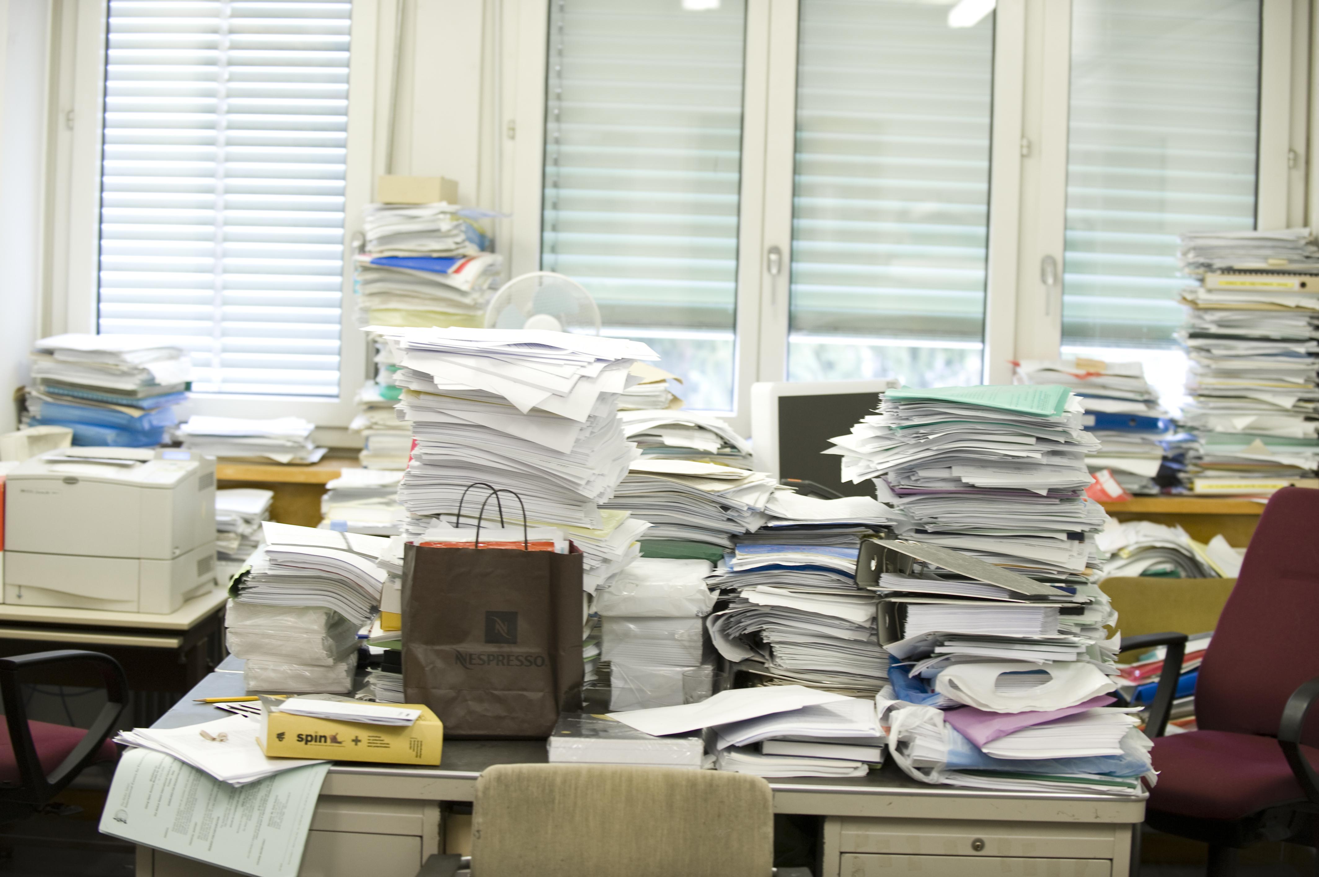 Messy desk with stacks of paperwork and binders, Cern, Geneva, Switzerland