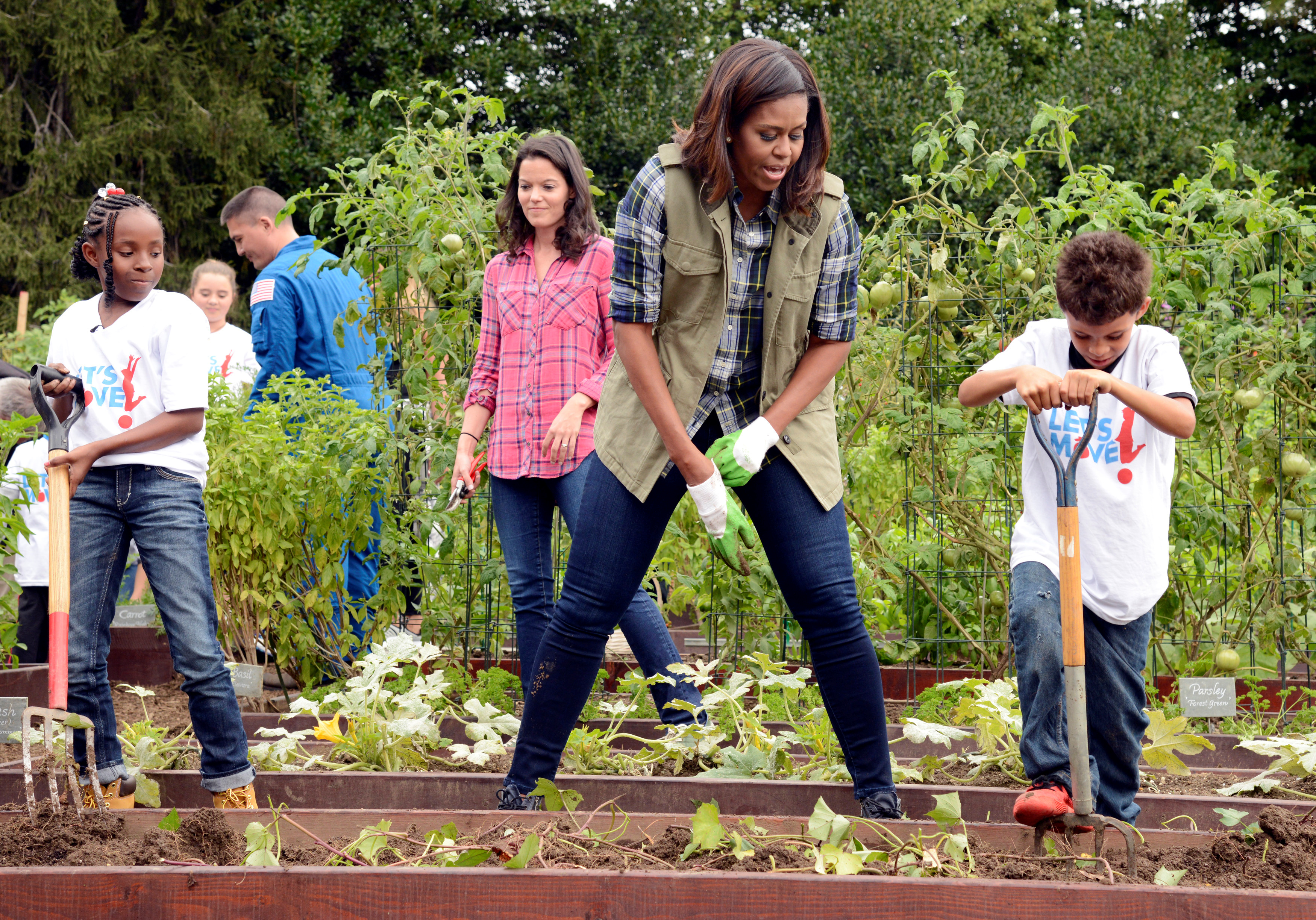 First Lady Michelle Obama encourages a youngster with a pitchfork as they harvest vegetables in the White House Kitchen Garden in Washington