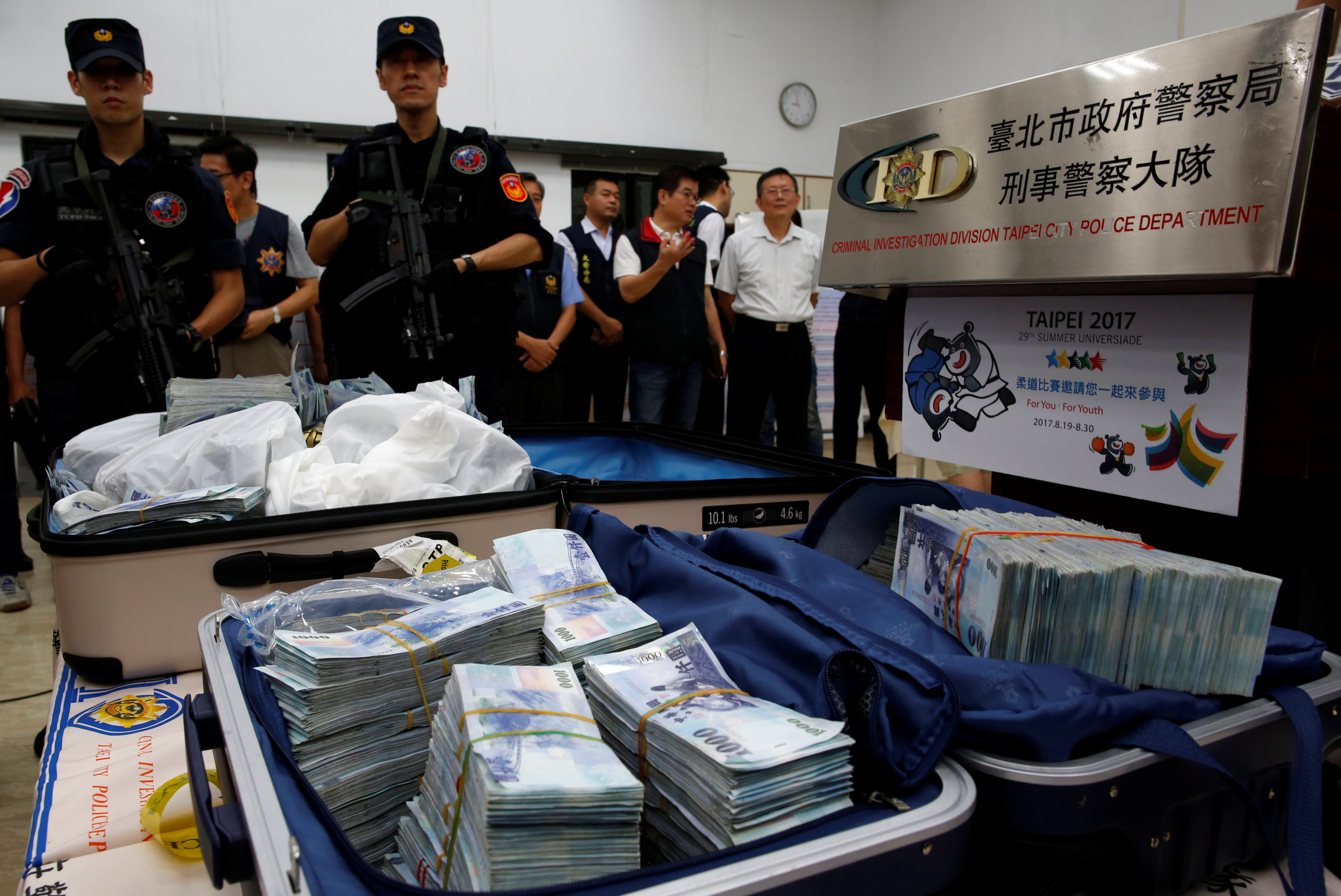 Taiwanese banknotes are displayed after they were found from a hotel room rented by one of the suspects involved in stealing from automated teller machines (ATM) in Taipei