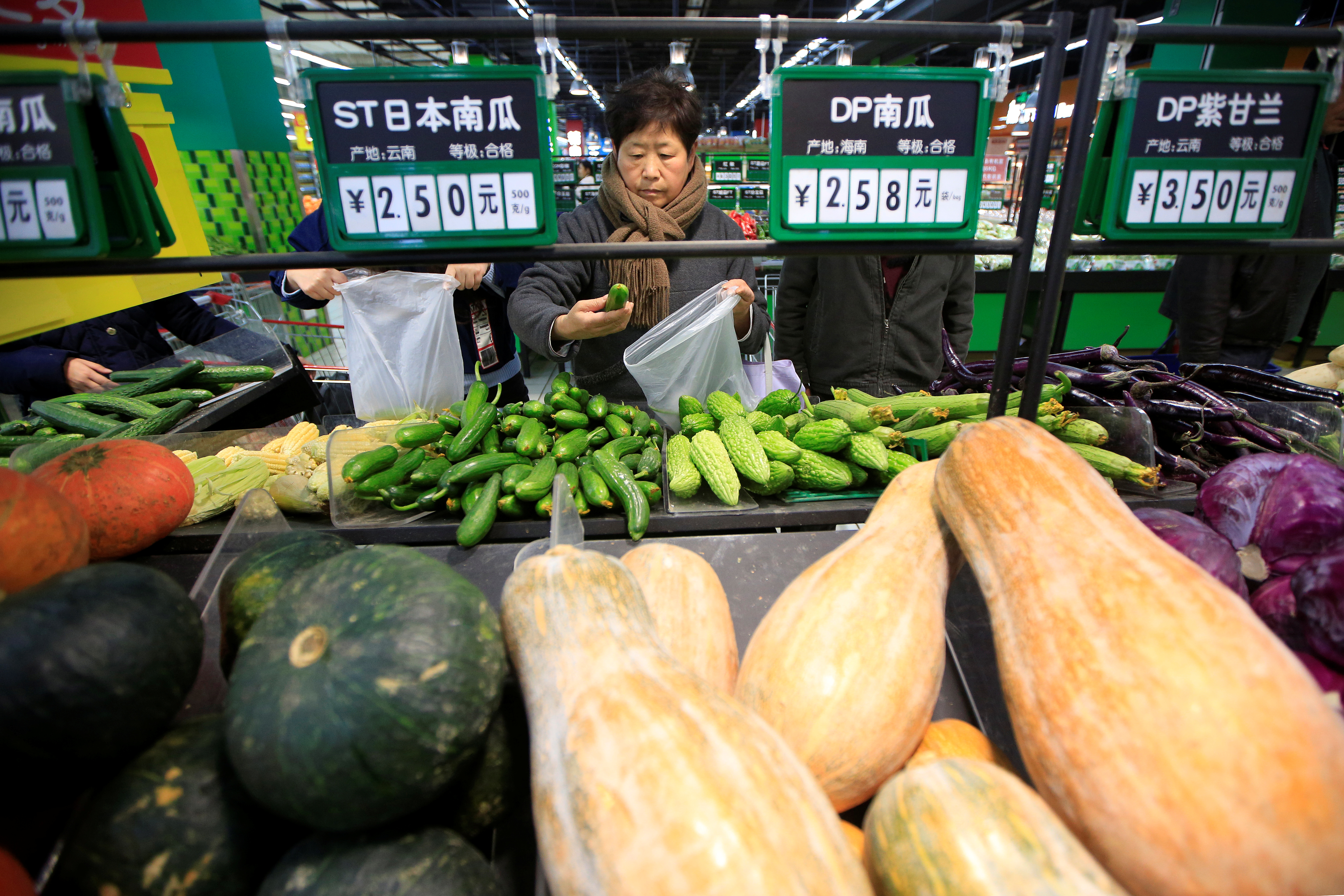 Consumers choose vegetables at a supermarket in Shanghai