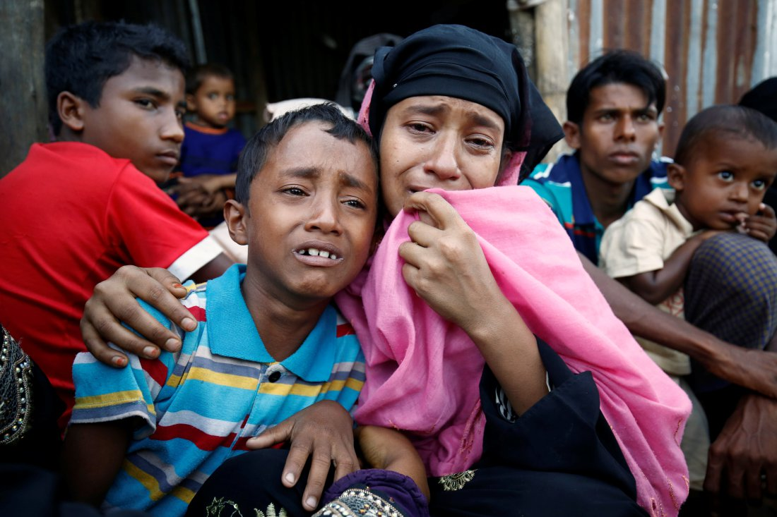 A Rohingya Muslim woman and her son cry after being caught by Border Guard Bangladesh while illegally crossing at a border check point in Cox's Bazar