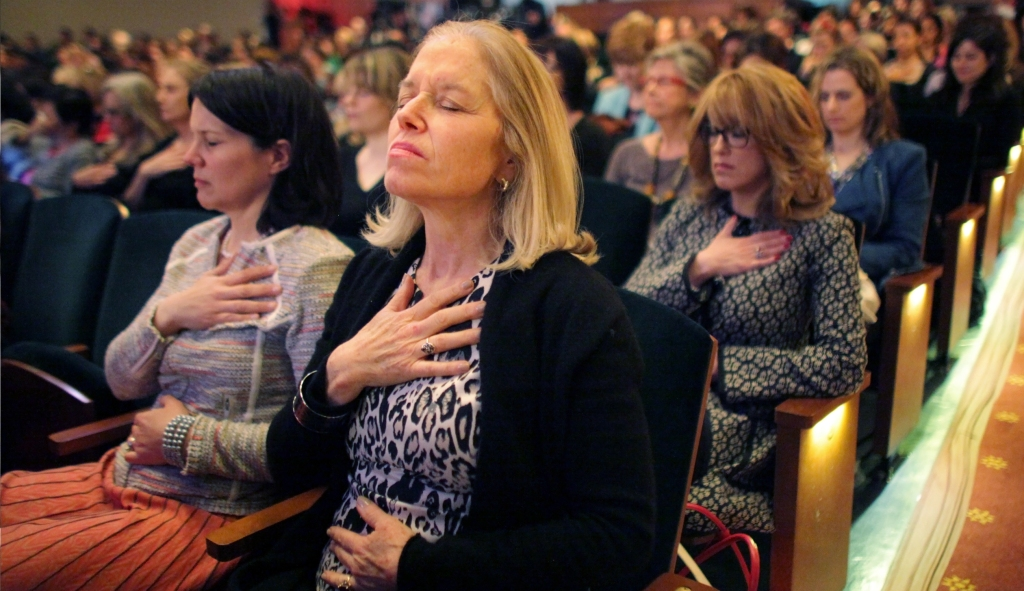 Audience members perform relaxation exercises under the guidance of Agapi Stassinopoulos, hostess Arianna Huffington's sister, during the THRIVE self-actualization seminar at the City Center in Manhattan, NY, 2014.